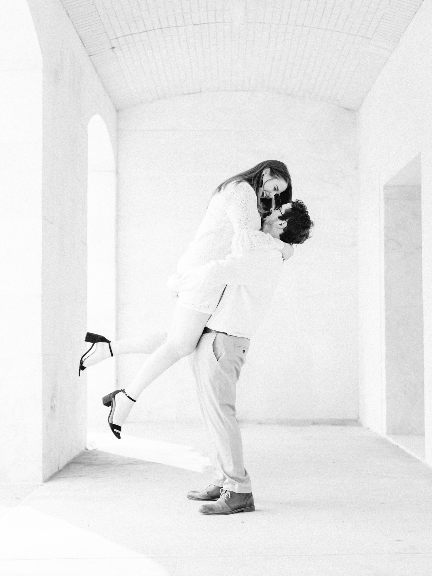 A man playfully lifts his woman off the ground as they laugh in a white marble corridor, after choosing the engagement photo location of the DIA in Detroit