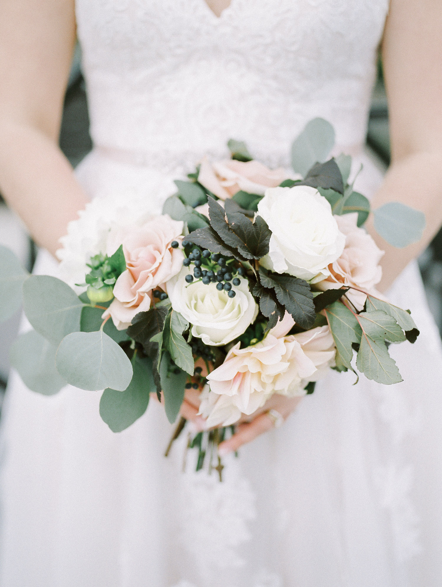 A bride holds a beautiful bouquet of white and pink roses, dahlias, berries, and seeded eucalyptus