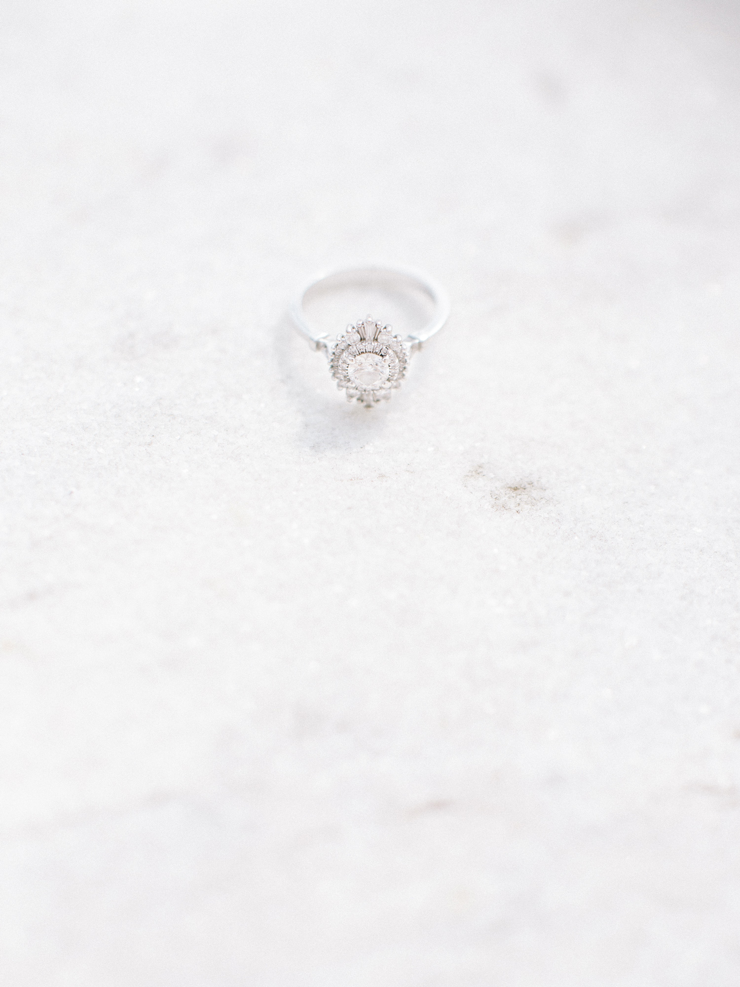 A beautiful art deco style engagement ring by Heidi Gibson sits on the white marble of the DIA in Detroit