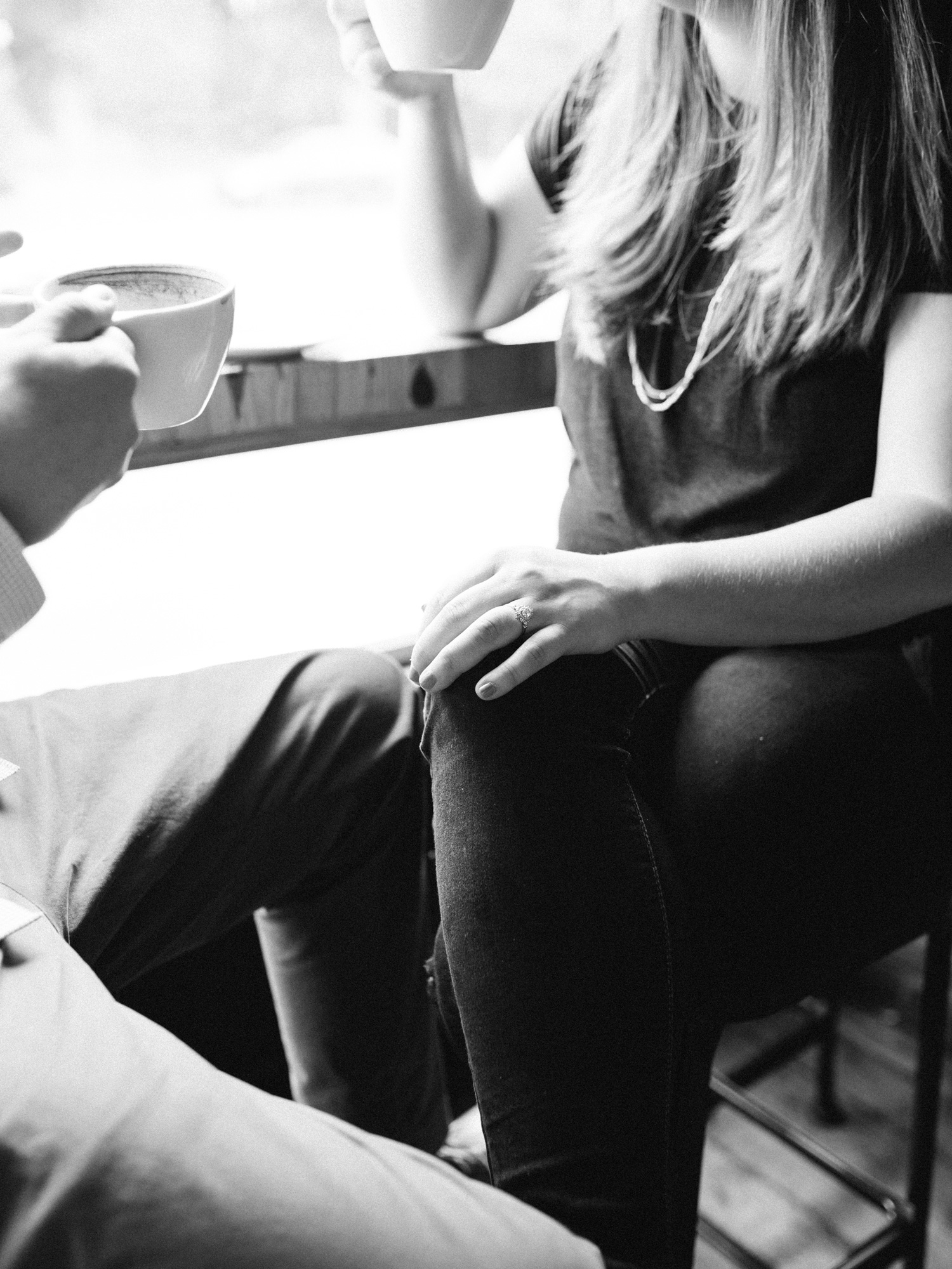 a black and white photo of a couple having coffee in downtown Detroit, focused on a woman's beautiful art deco engagement ring