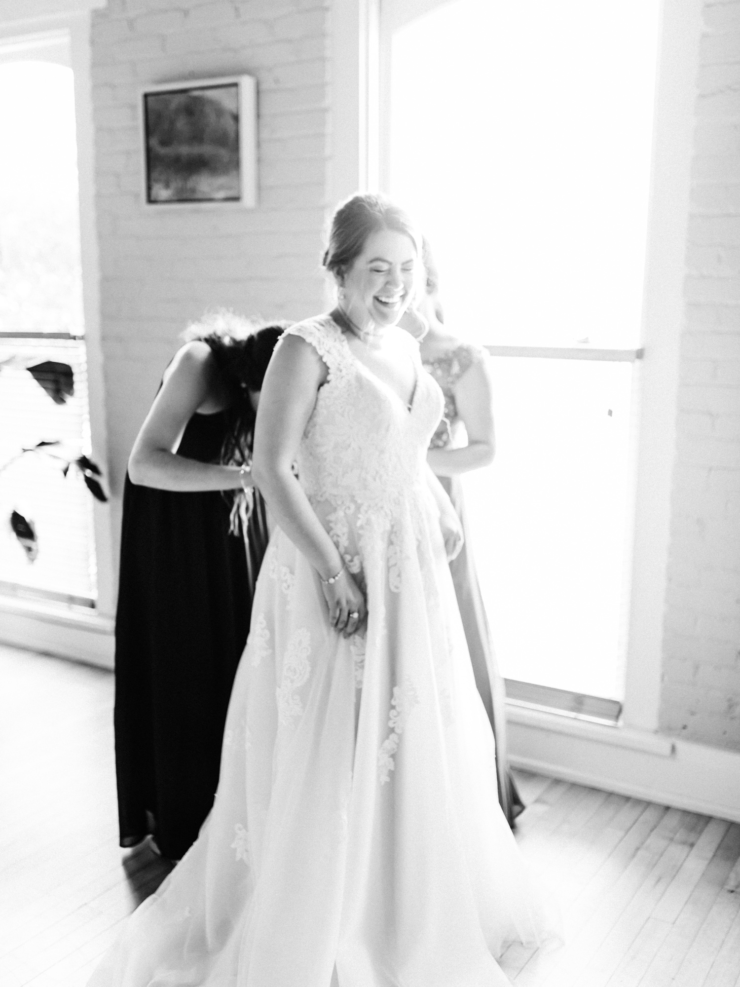 an excited bride smiles as bridesmaids help tie the back of her wedding gown