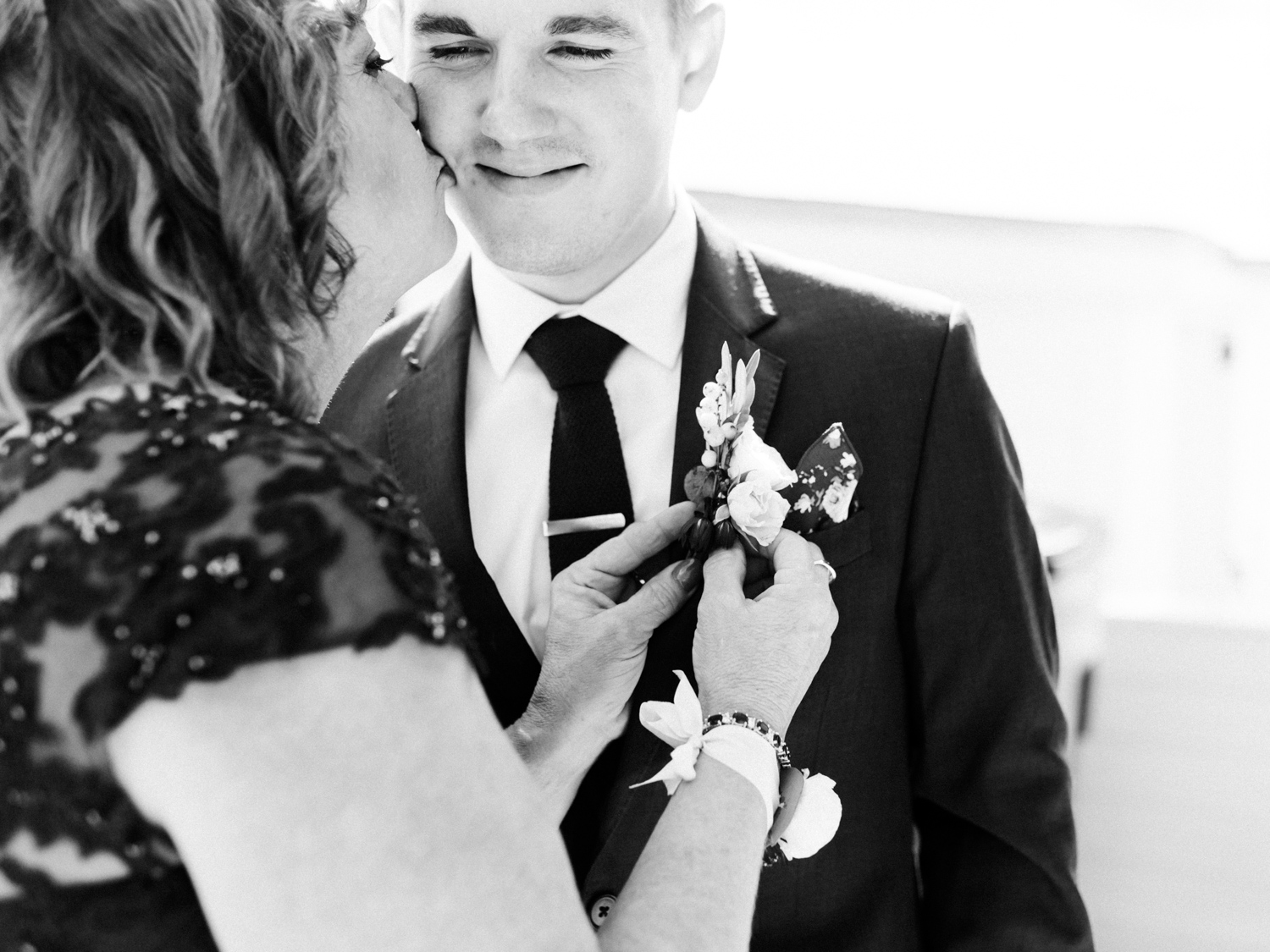 A groom's mother kisses his cheek while fastening his boutonniere