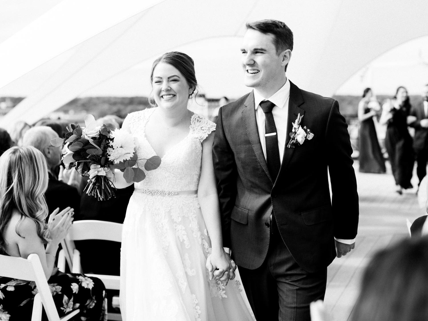 A smiling, newly-married couple holds hands and walks back down the aisle
