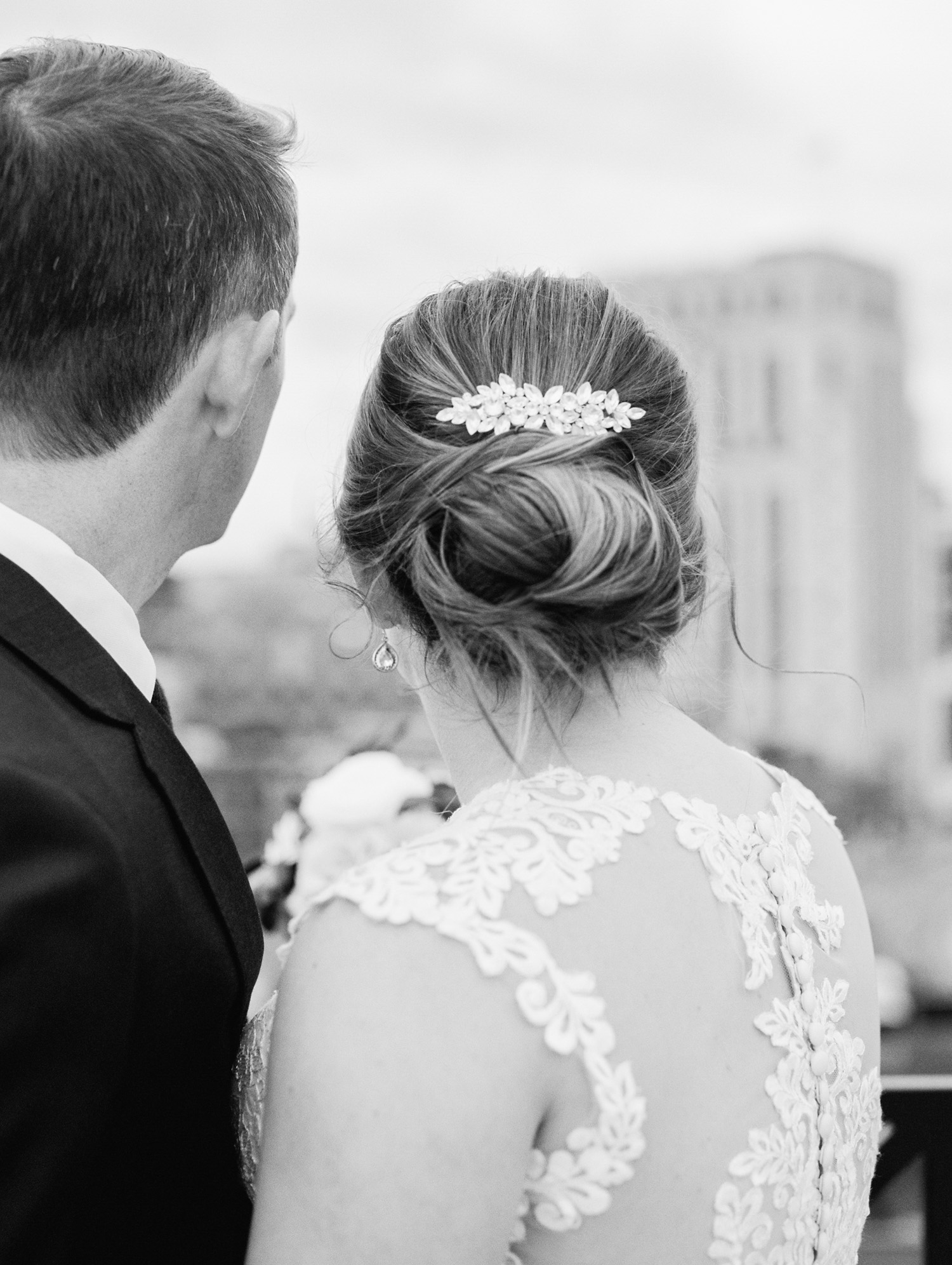 A bride and groom photographed from behind, featuring the bride's beautiful crystal headpiece