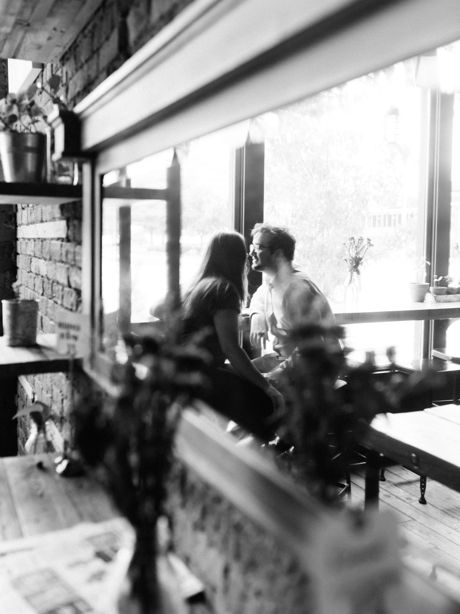A couple is reflected in a mirror at Great Lakes Coffee in Detroit as they lean in to share a kiss at their engagement photo session