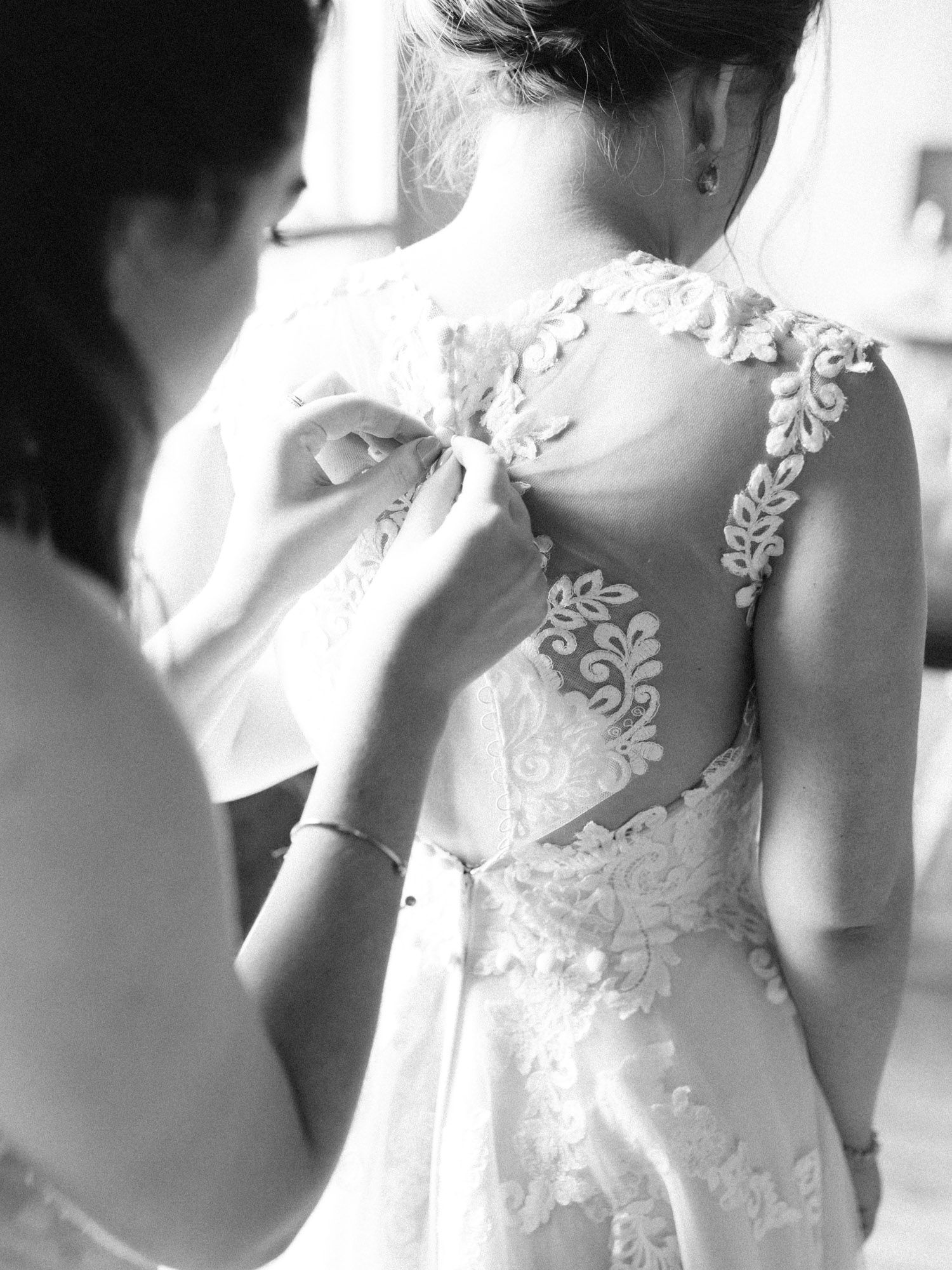 The maid of honor fastens the buttons on the back of the bride's lace wedding gown