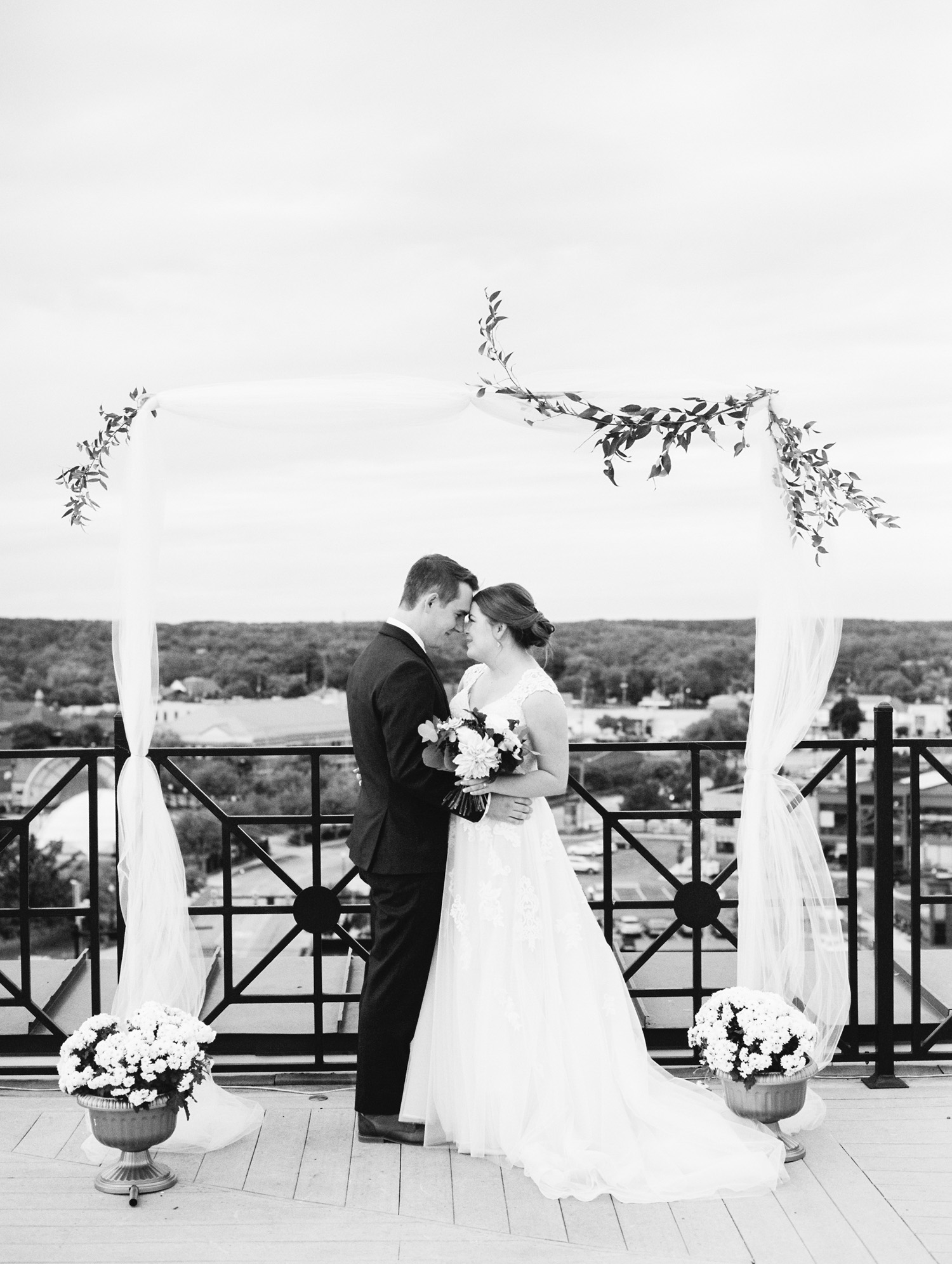 A couple embraces under the ceremony arch on a downtown Kalamazoo rooftop