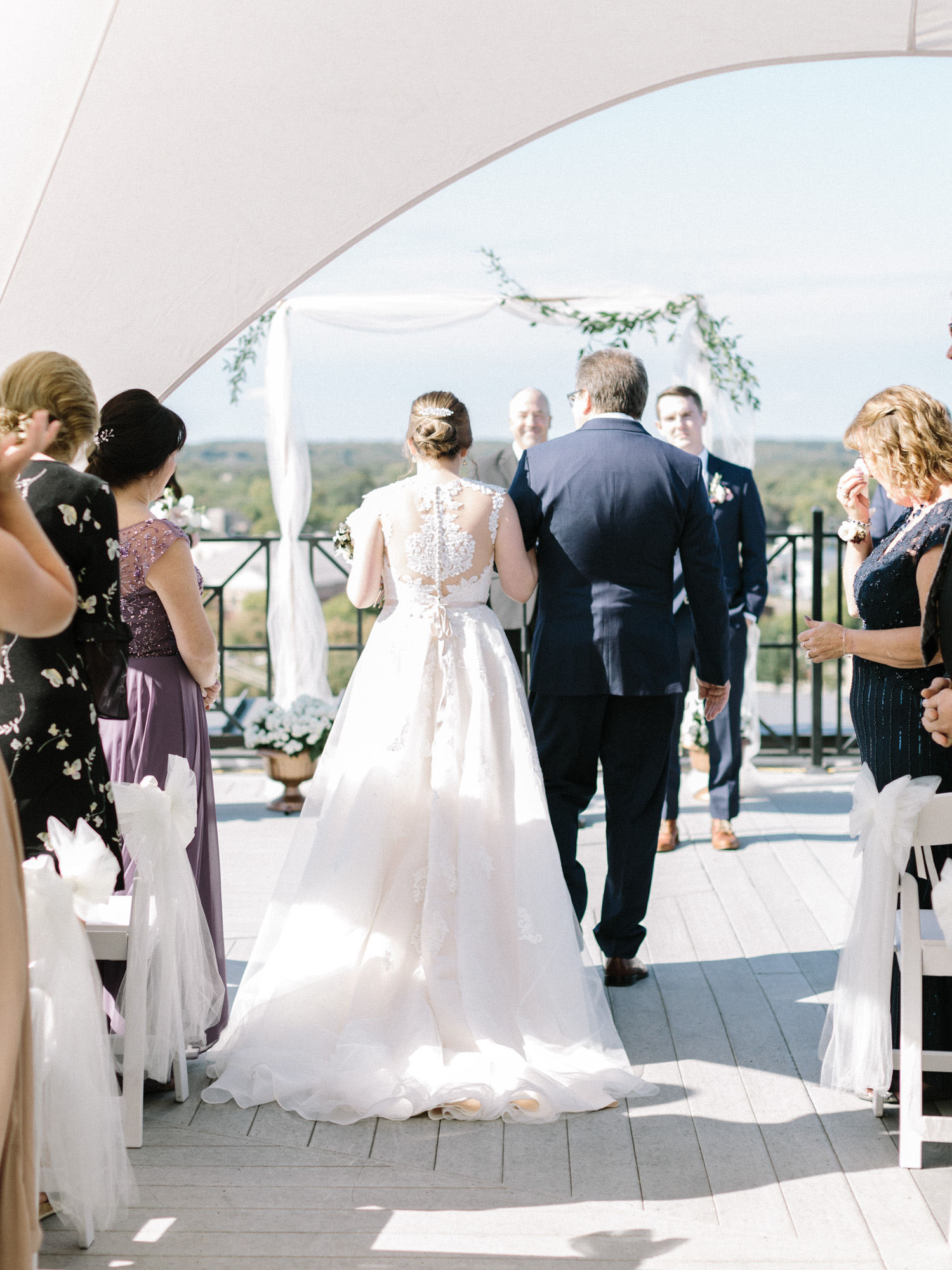 The view from behind as a bride in an ornate lace gown walks down the aisle on the rooftop of Loft 310