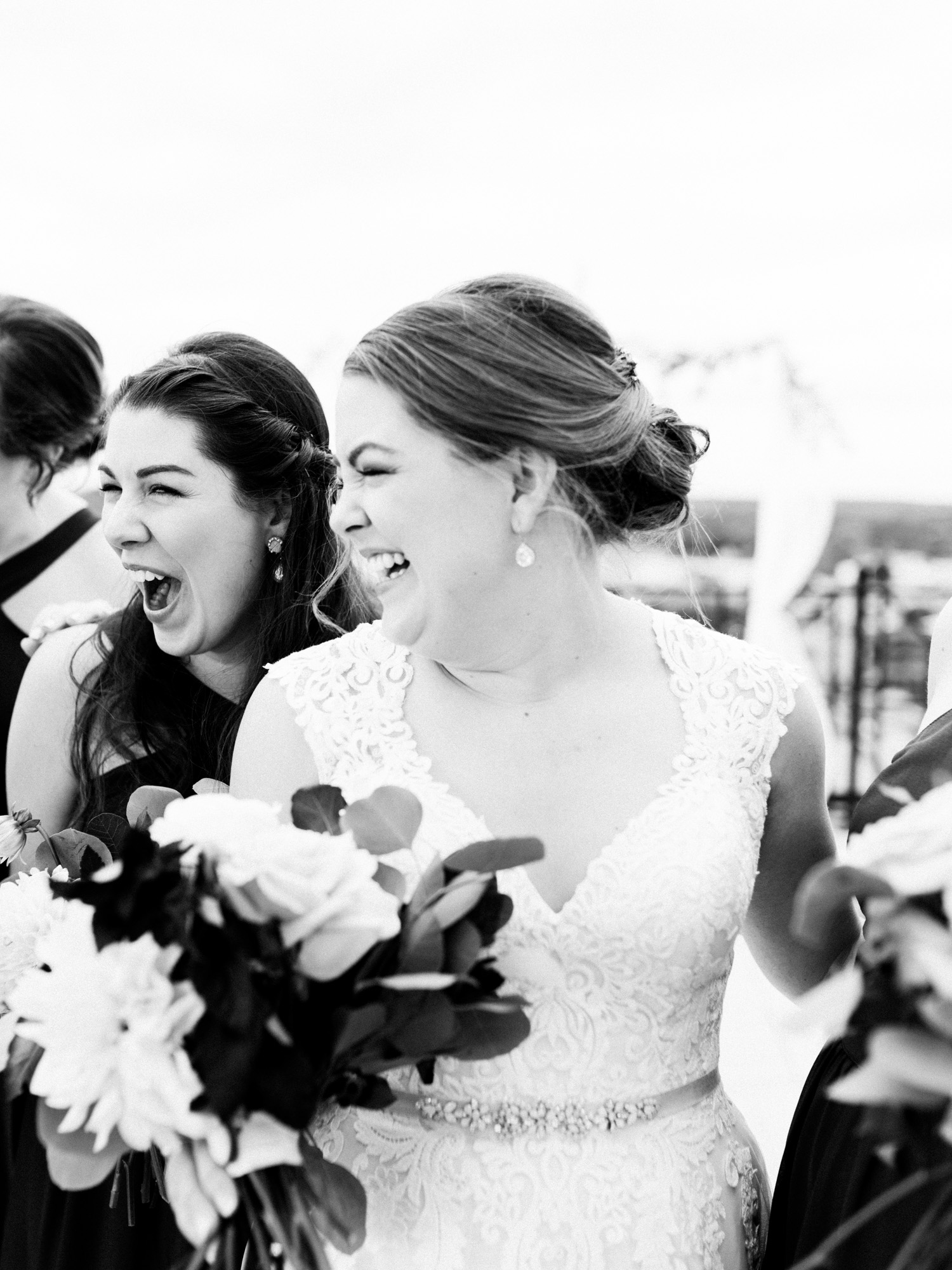 A bride laughs hard with her maid of honor on a rooftop