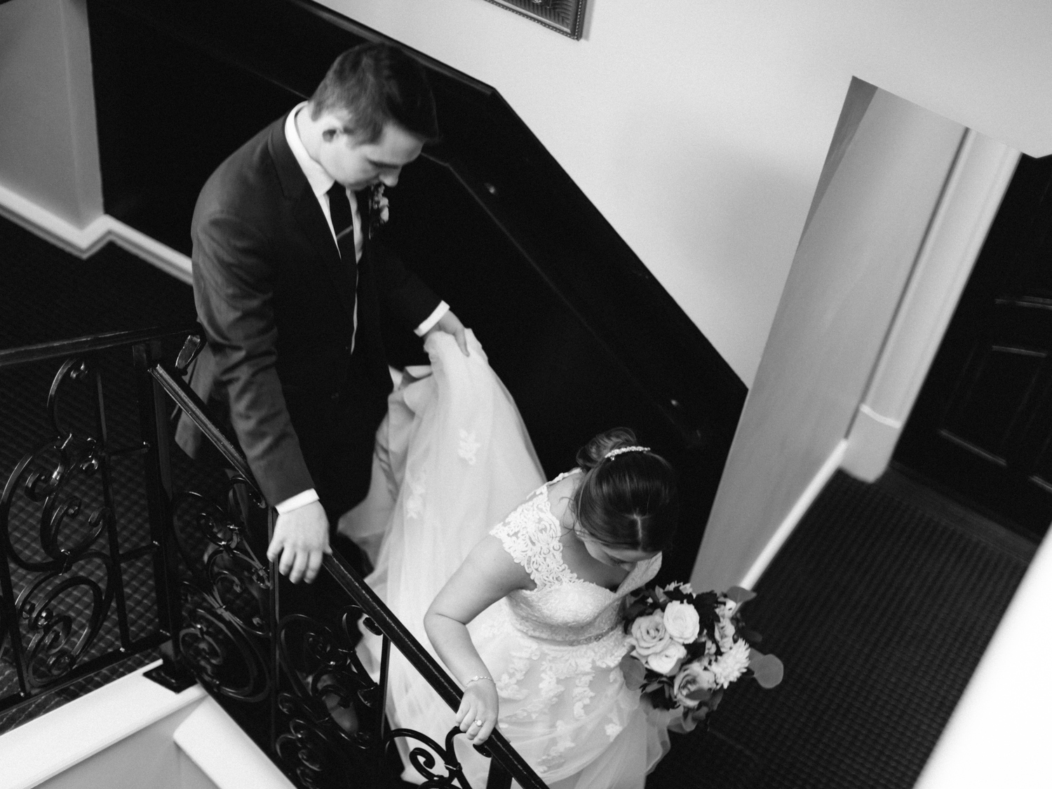A groom carries his bride's dress as they walk down stairs at Loft 310