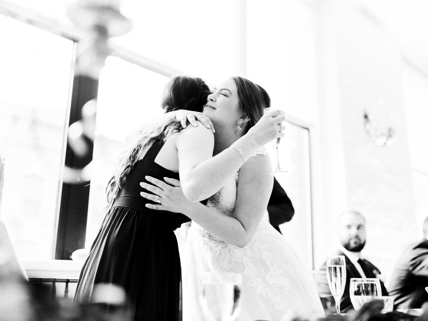 A bride and her sister share an embrace after her speech at Loft 310