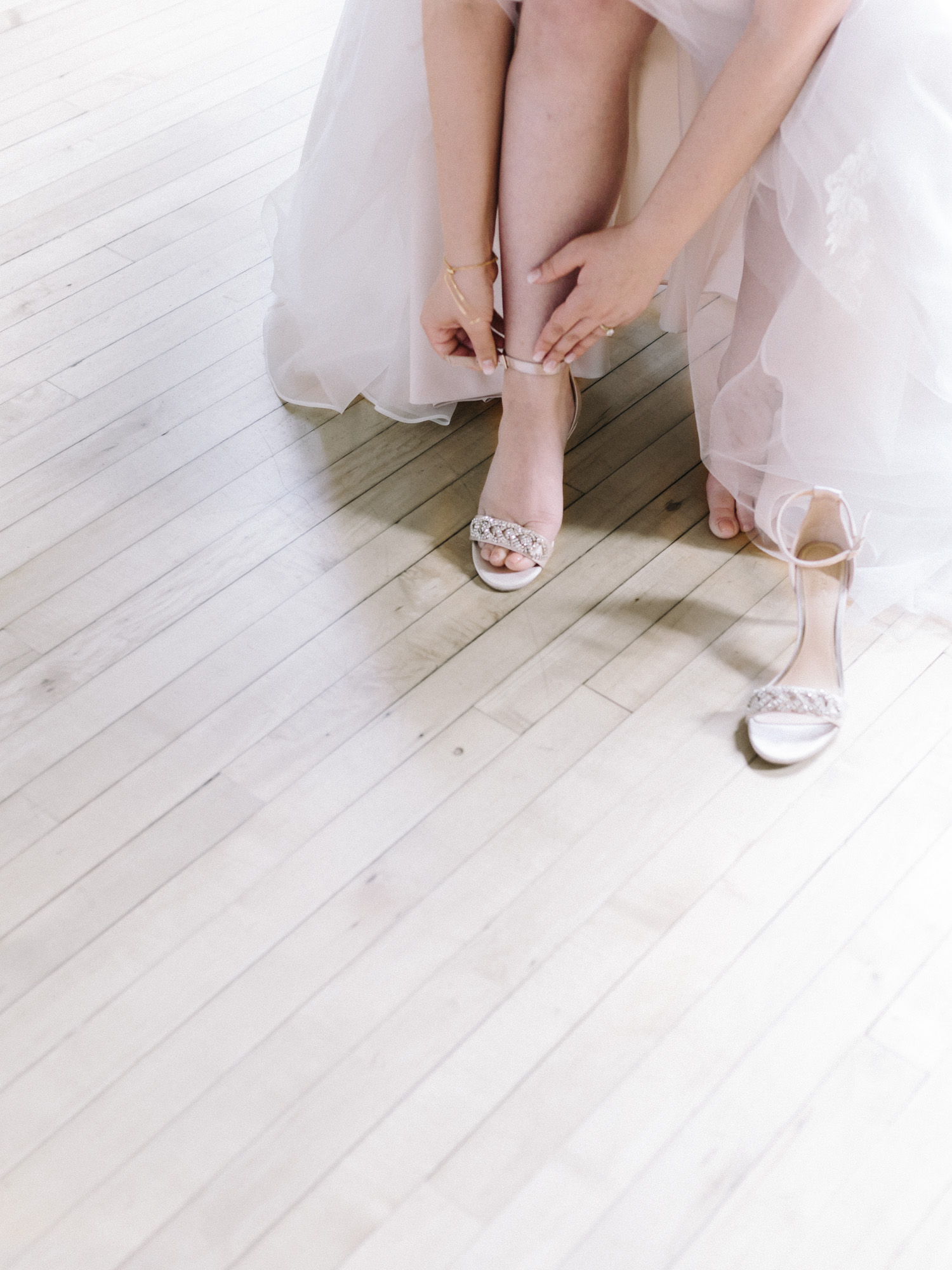 A bride fastens her sparkly wedding shoes on a wood floor