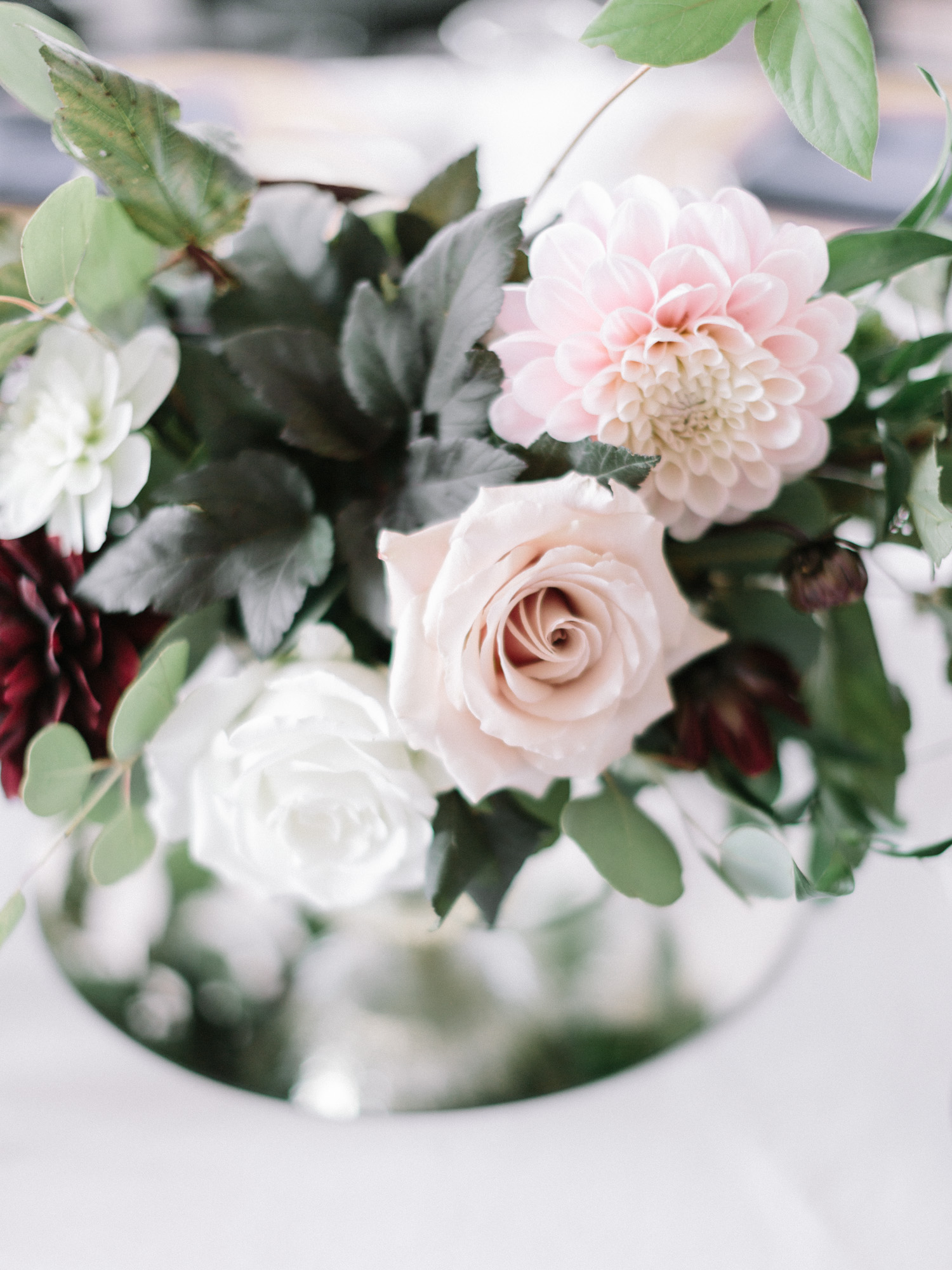 A wedding reception centerpiece with greenery, pink dahlias, and blush roses at loft 310