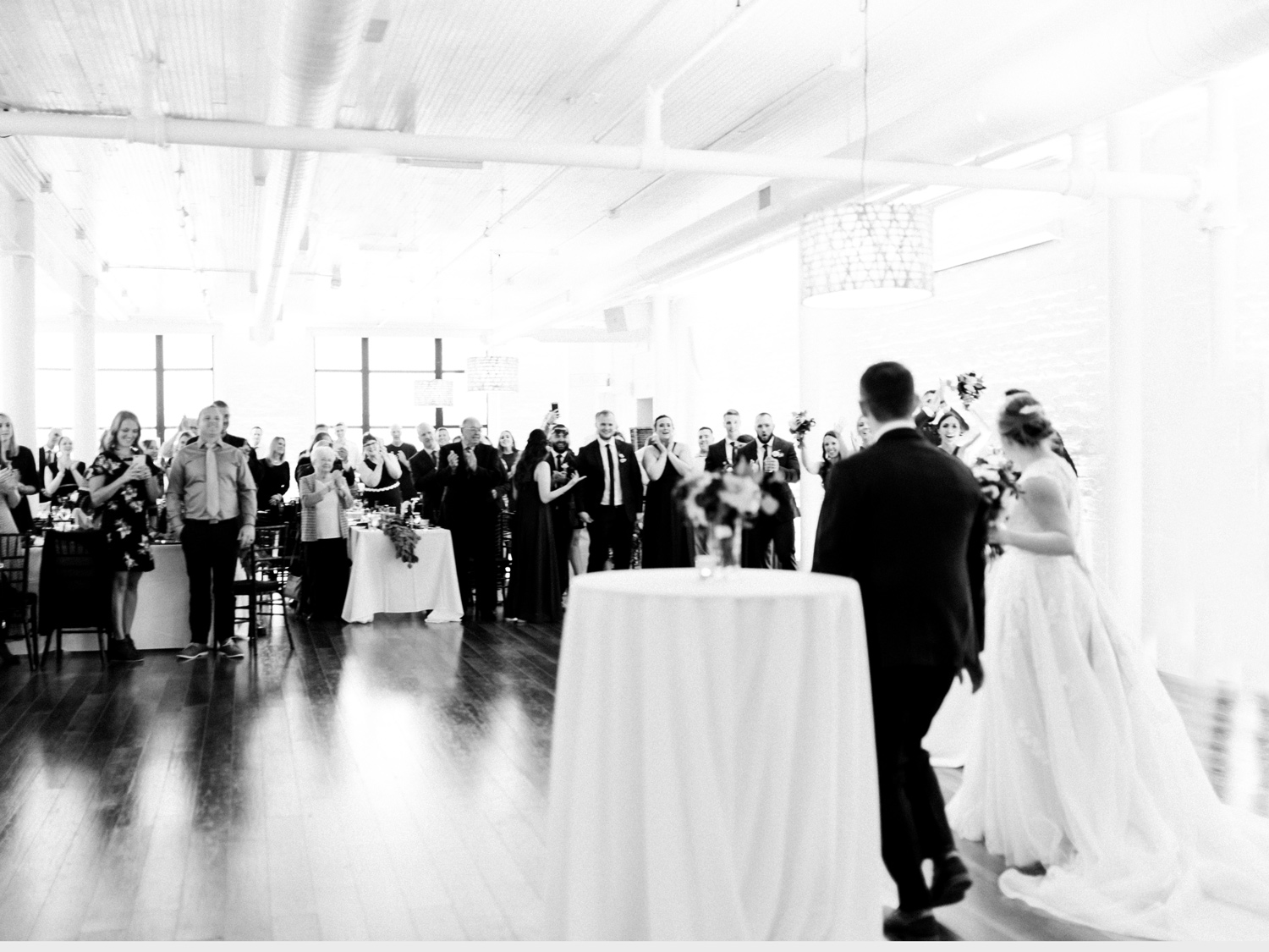 A couple is welcomed into their Loft 310 wedding reception by cheering guests