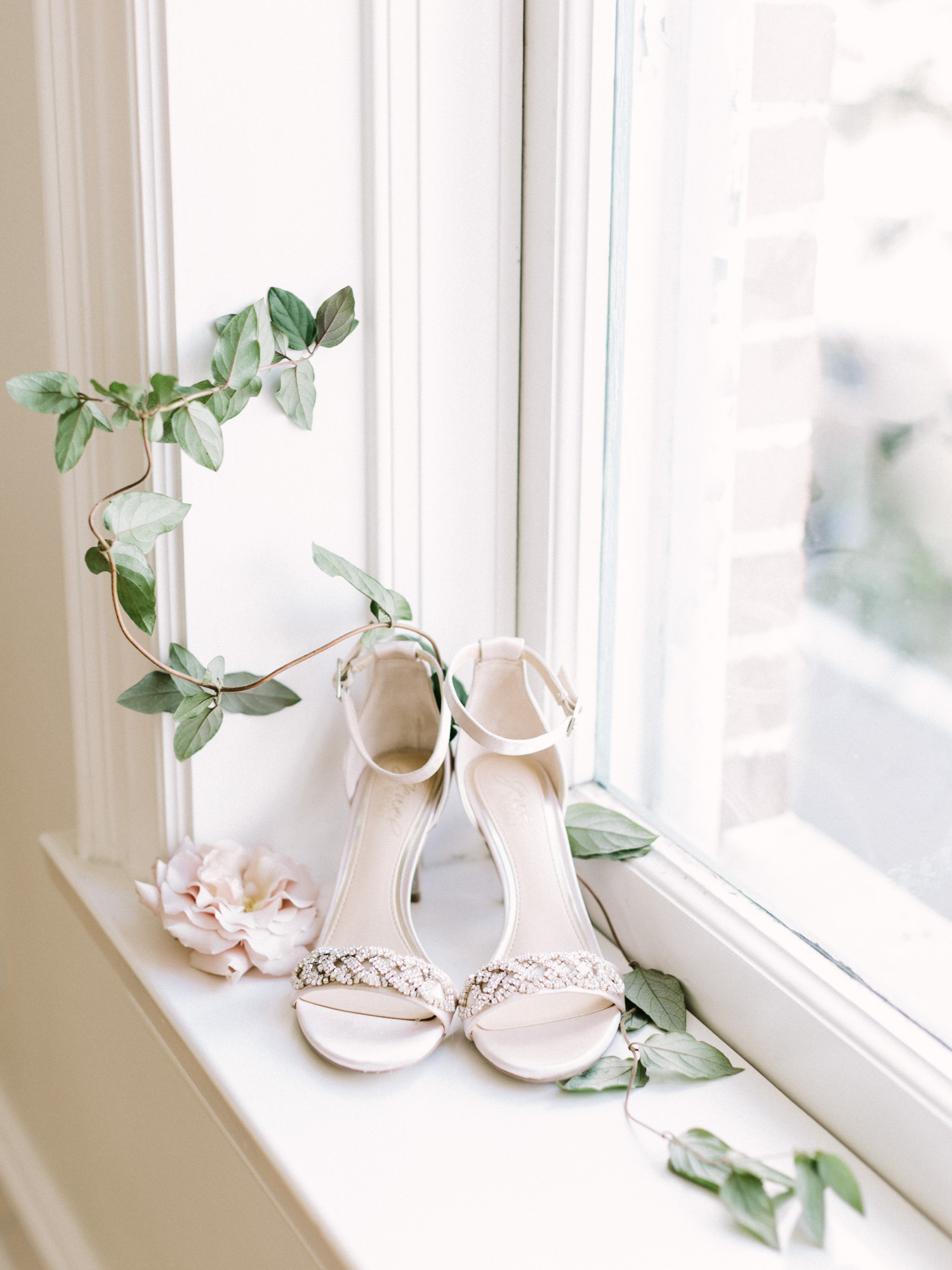 beautiful champagne wedding shoes with sparkle rest in a windowsill with flowers and greenery