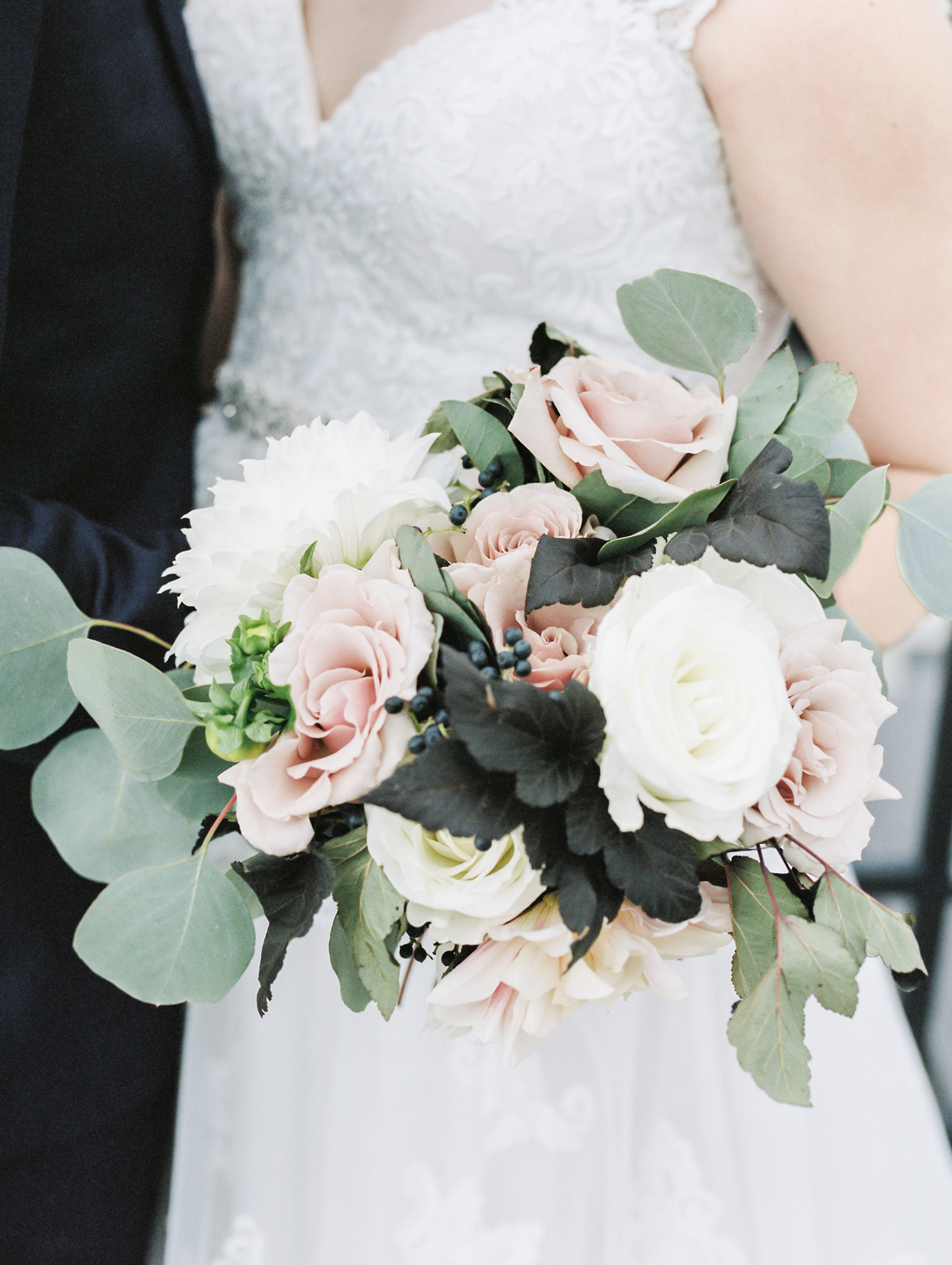 A beautiful bridal bouquet with seeded eucalyptus, and white and pink roses and dahlias
