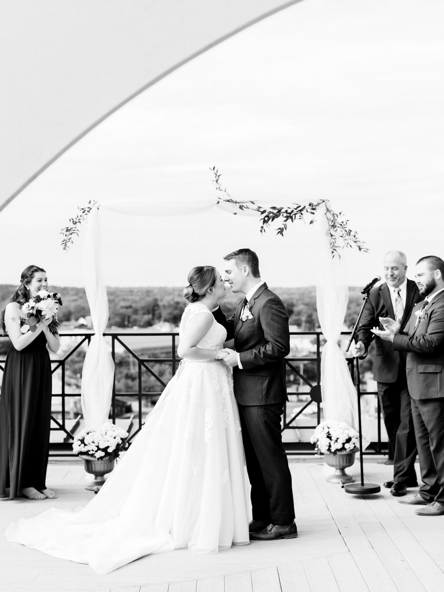 A wedding couple leans in for their first kiss during their rooftop ceremony at Loft 310 in Michigan