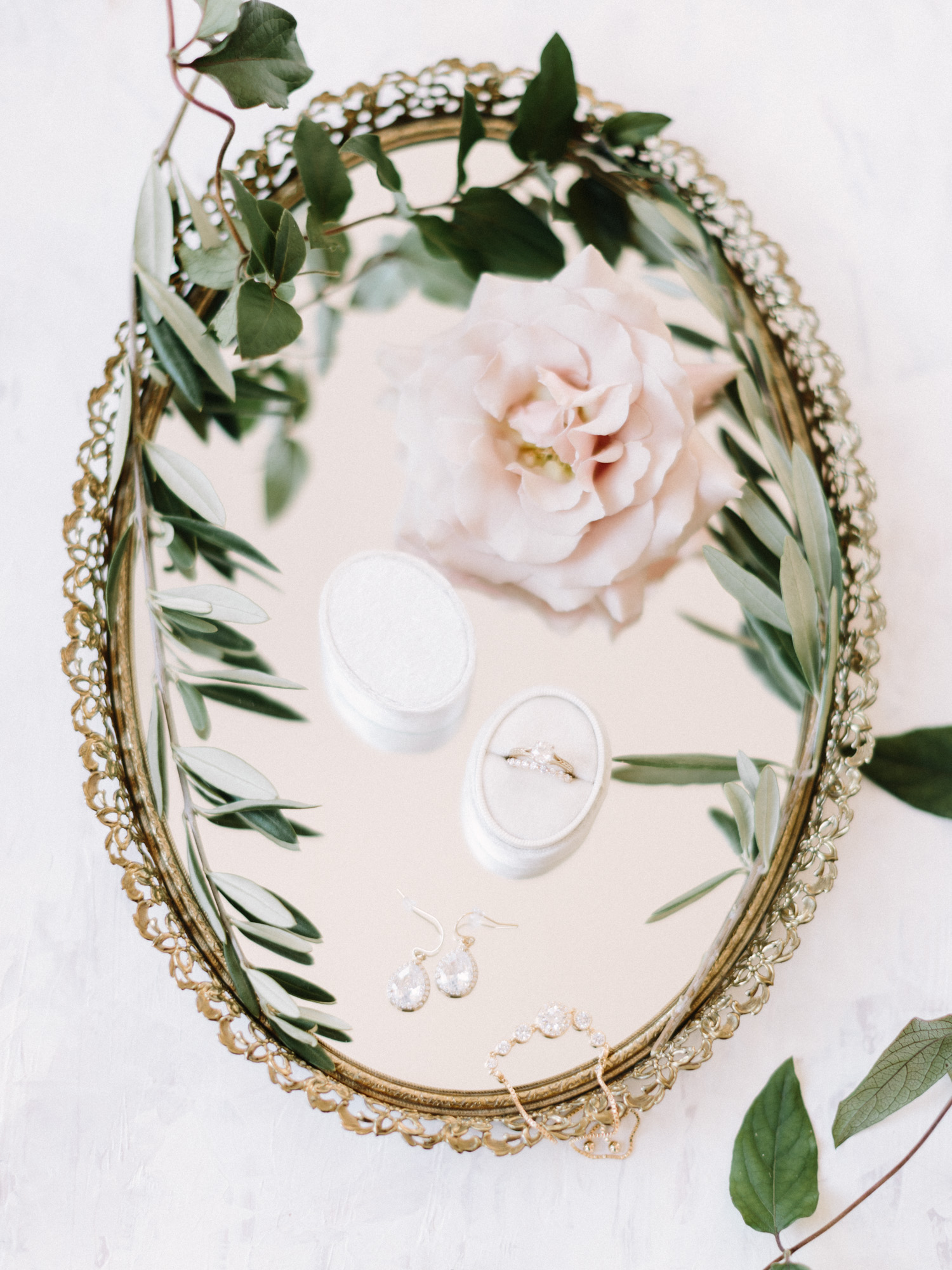 gold bridal jewelry rests on an antique mirror with greenery and flowers
