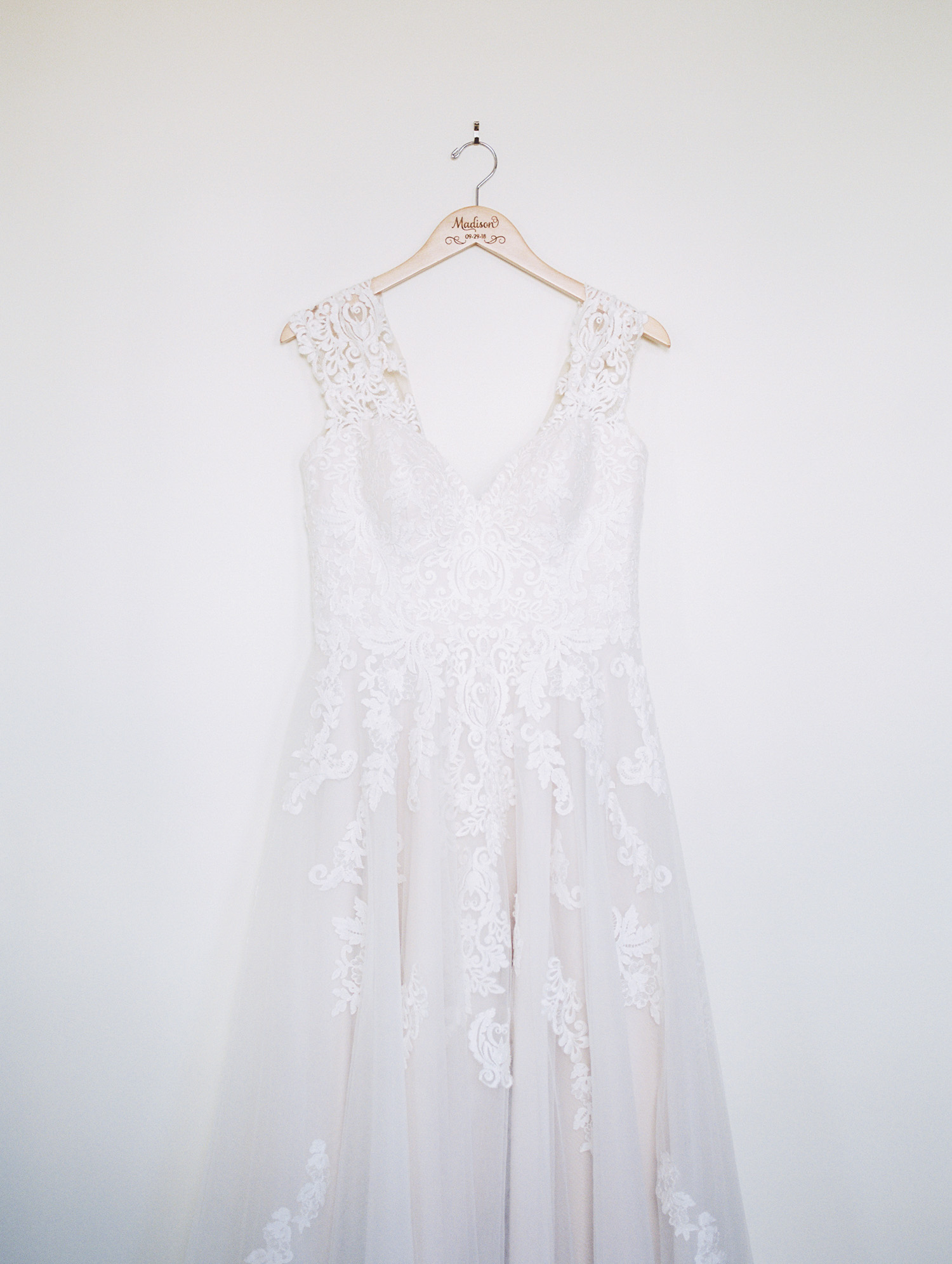 A beautiful lace wedding gown hangs on a white wall