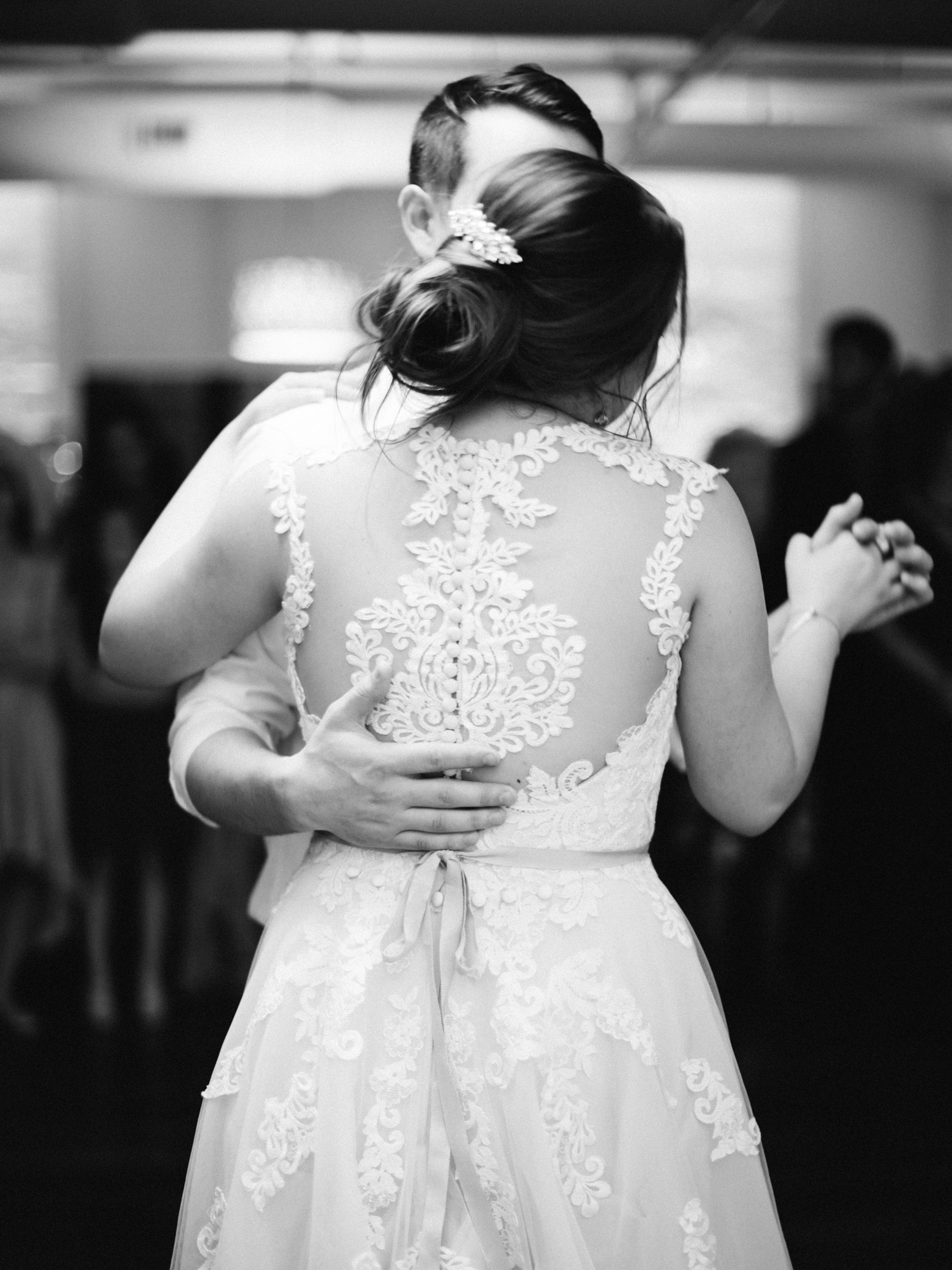 The intricate lace detail of a bride's gown is shown as she dances with her groom