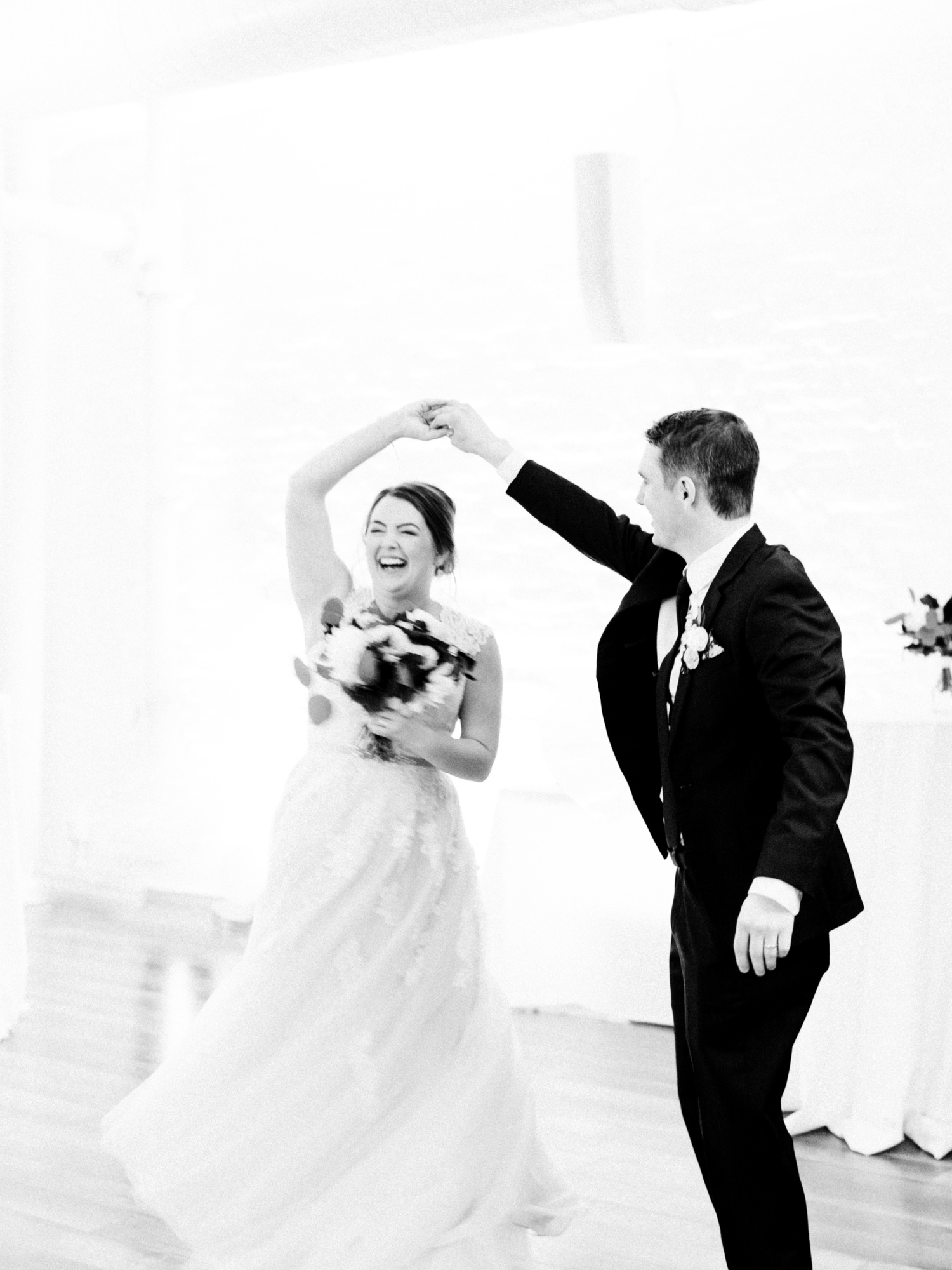 A bride laughs as her groom twirls her as they enter their Loft 310 wedding reception