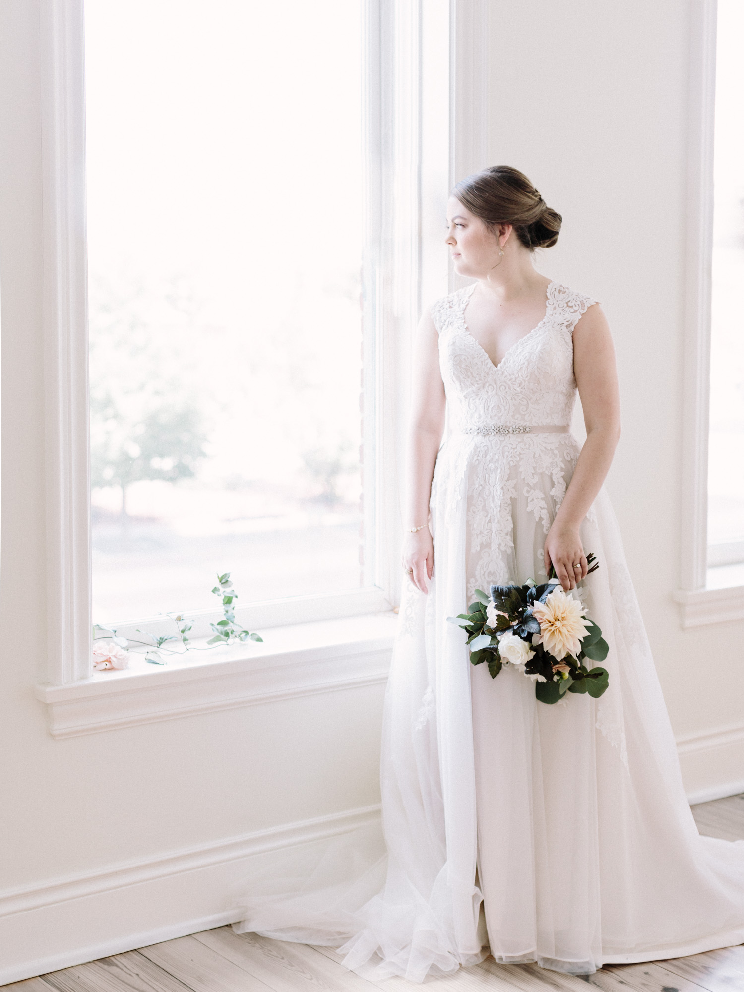 A bride gazes out the window with her bouquet in downtown Kalamazoo
