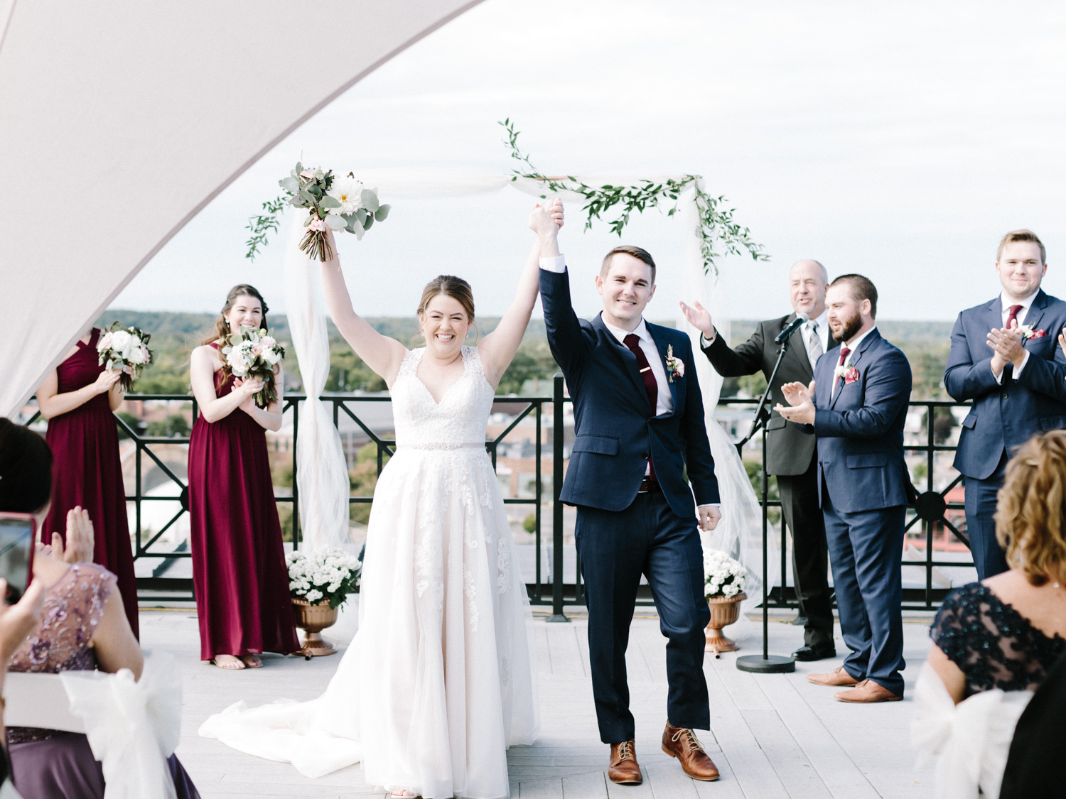A couple raises held hands in joy after being pronounced married at their rooftop ceremony at Loft 310