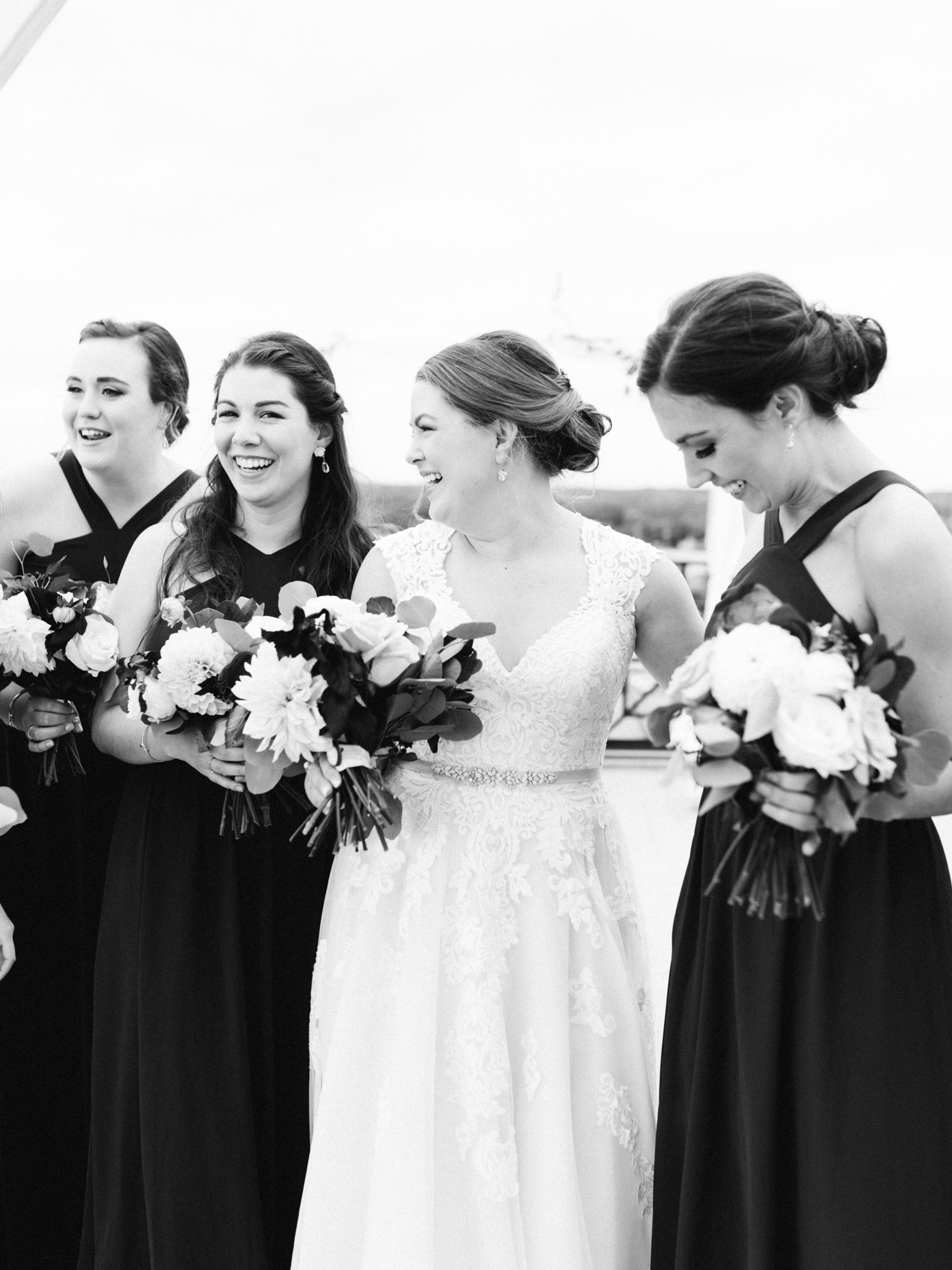 A bride laughs with her bridesmaids on a downtown Kalamazoo rooftop