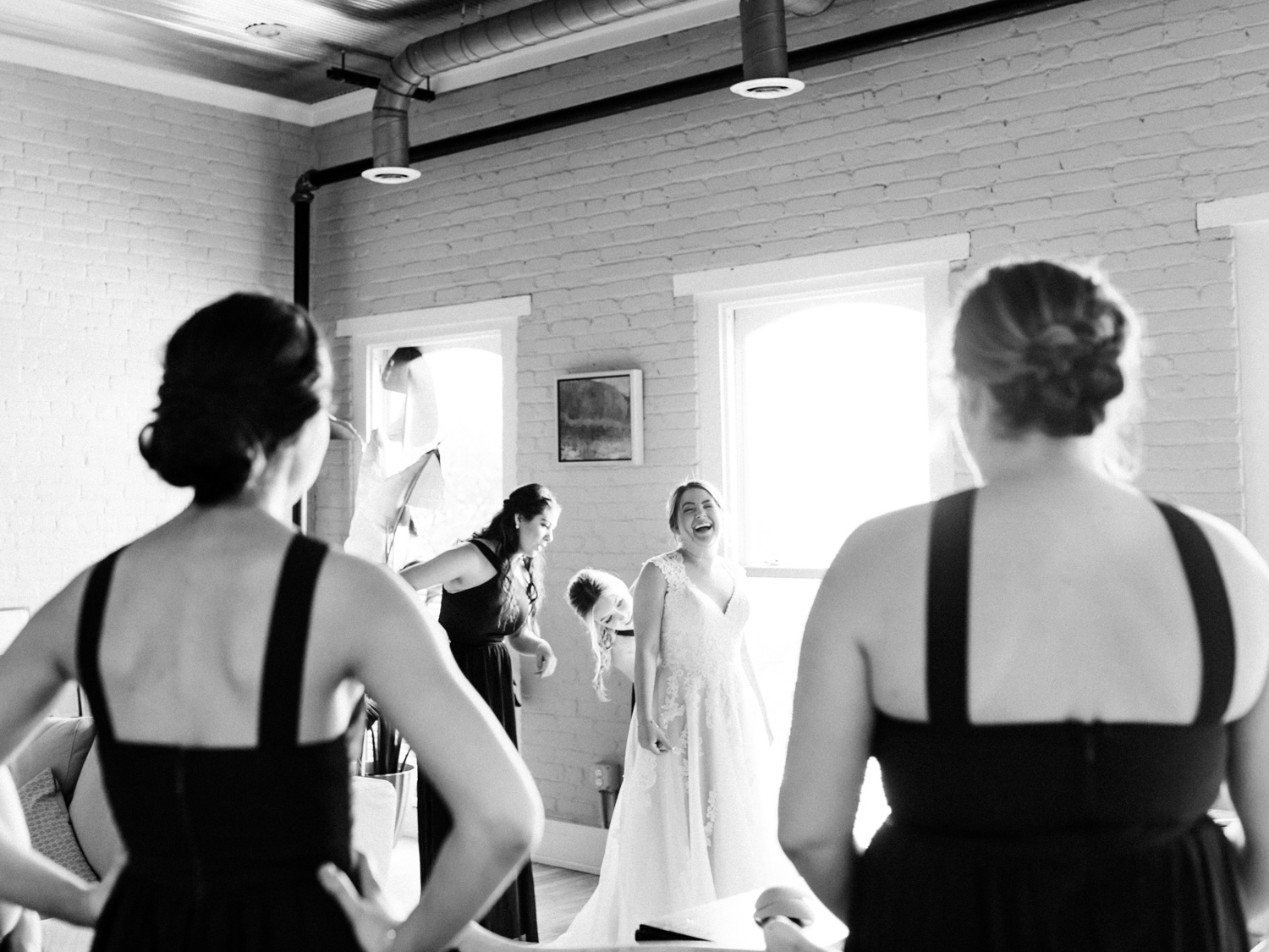 A bride laughs while getting ready for her downtown Kalamazoo wedding