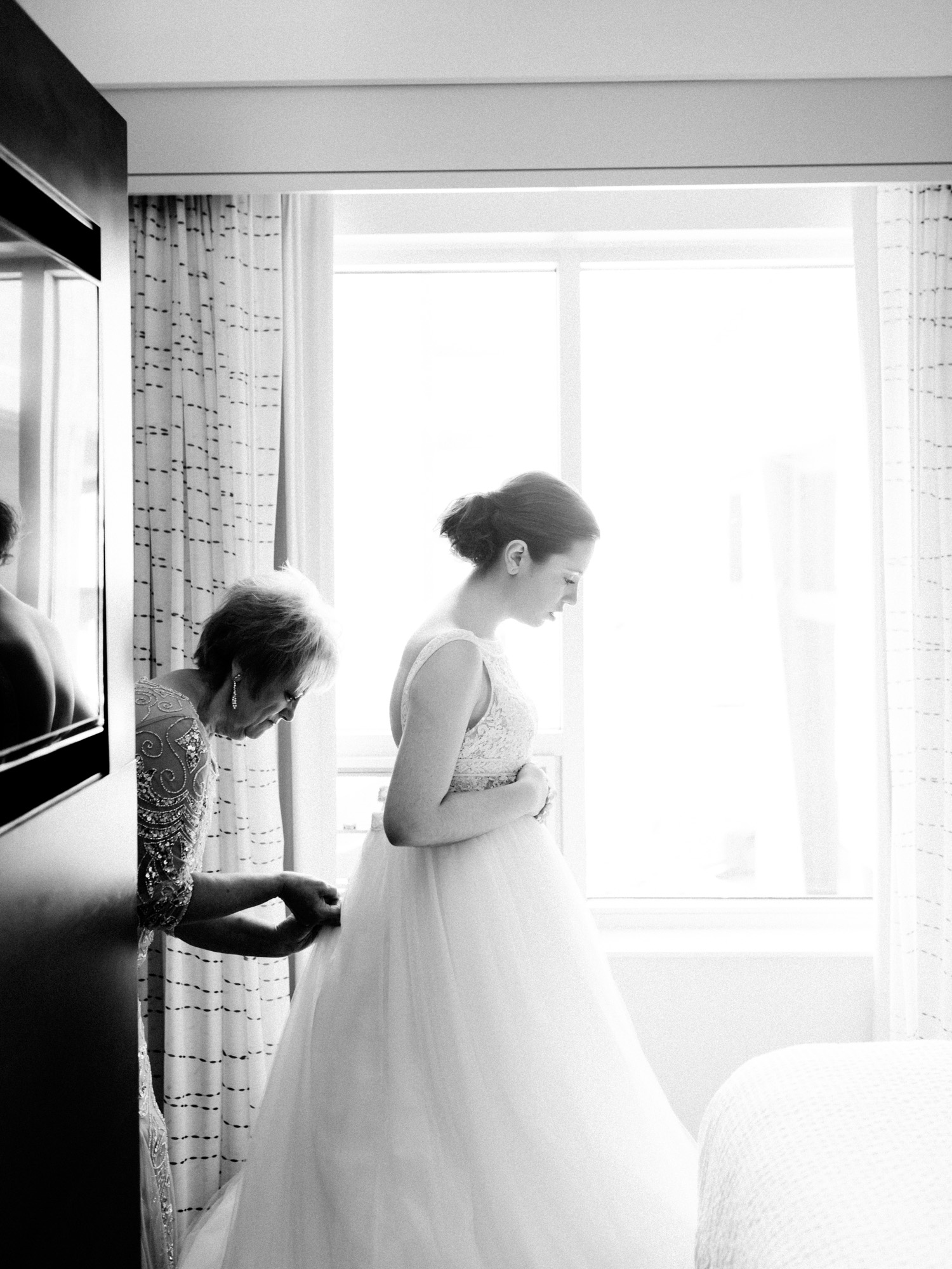 A bride stands in window light at an Ann Arbor hotel as her mother fastens the back of her dress