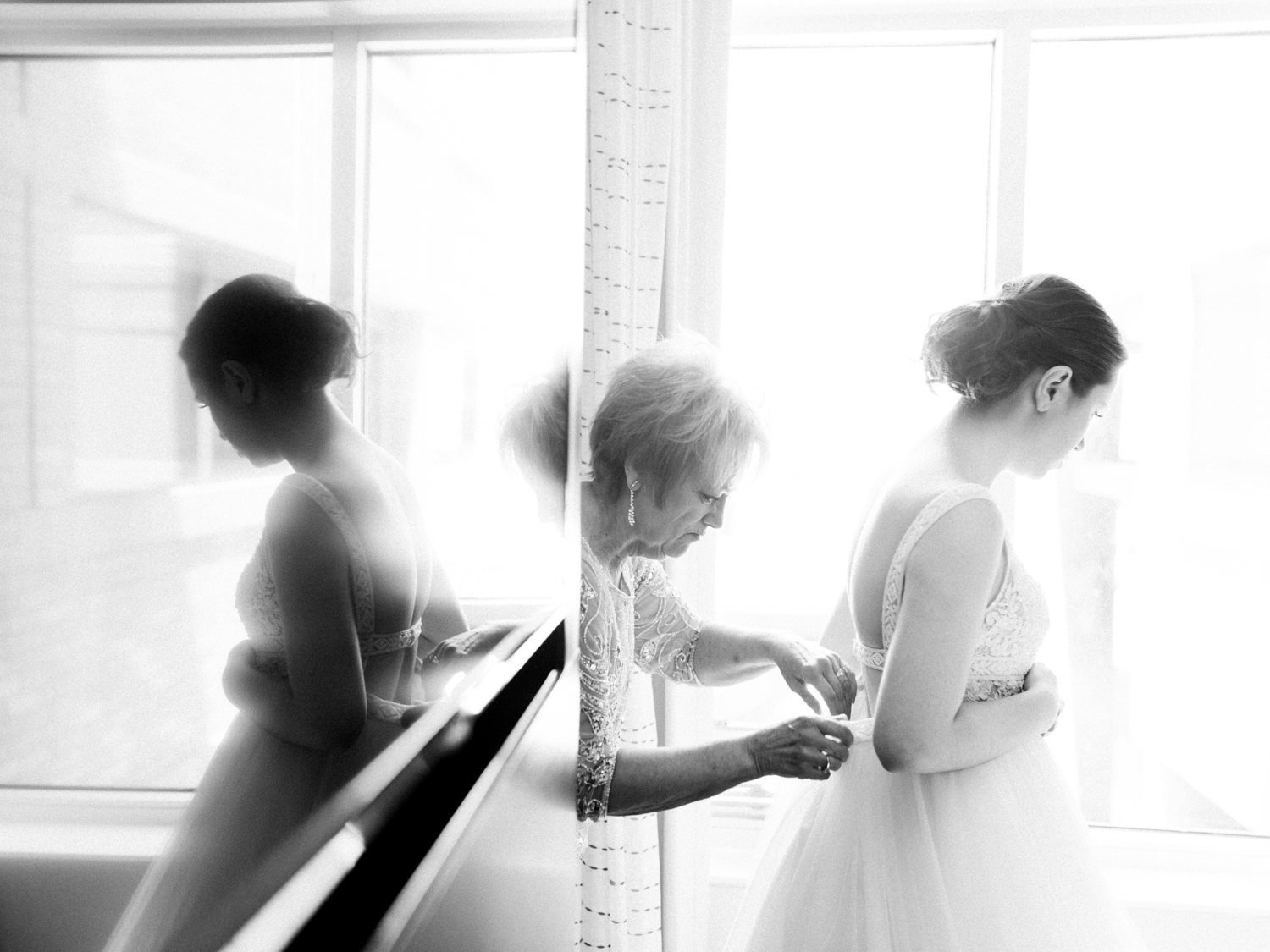An artistic photo with reflections shows a mother helping her daughter into her wedding dress in Michigan