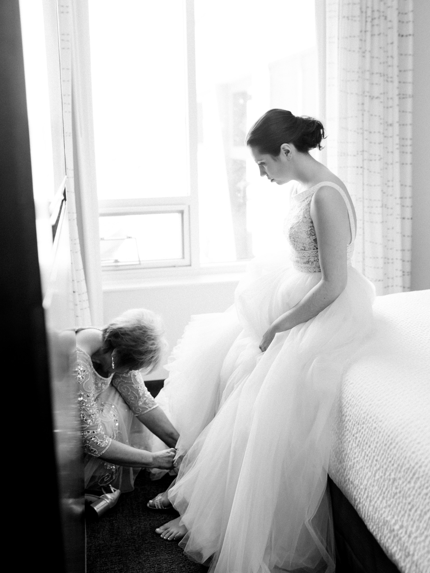 A bride sits on the hotel bed as her mother helps fasten her shoes in Ann Arbor, Michigan