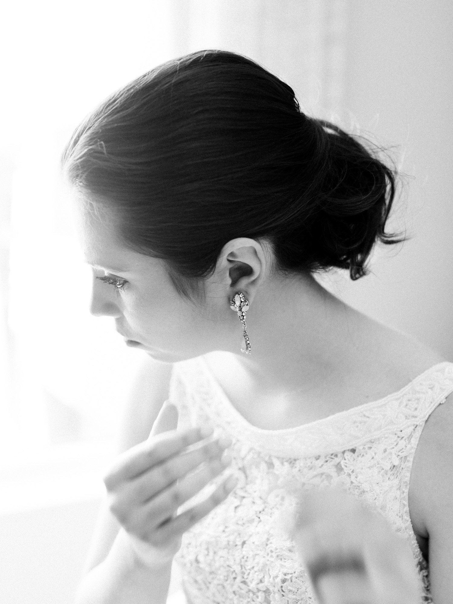 Luminous window light envelops a bride as she fastens her earrings on her wedding day in Ann Arbor, Michigan