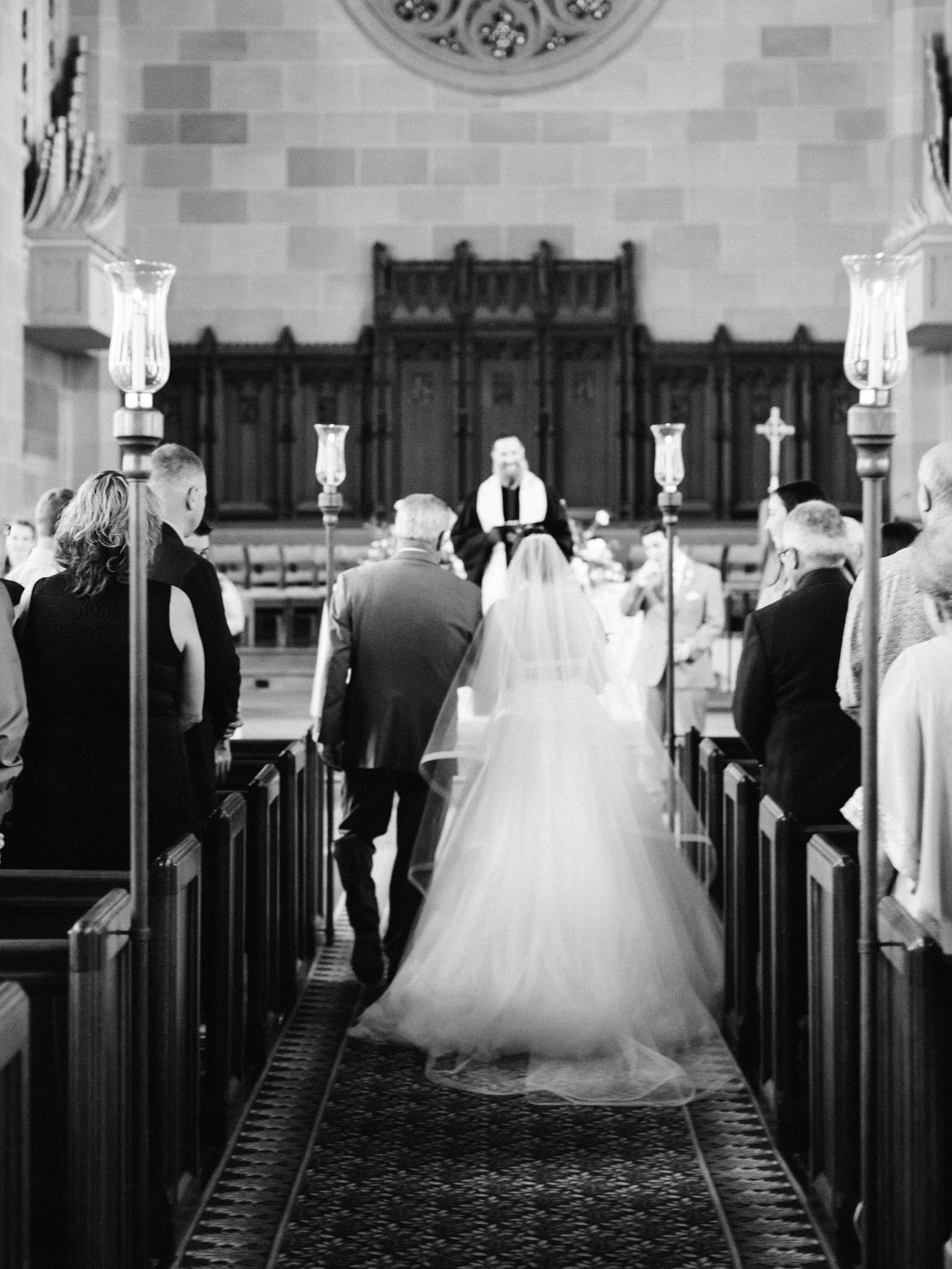 The view from behind the bride and her father as they walk down the church aisle on her wedding day in Ann Arbor, Michigan