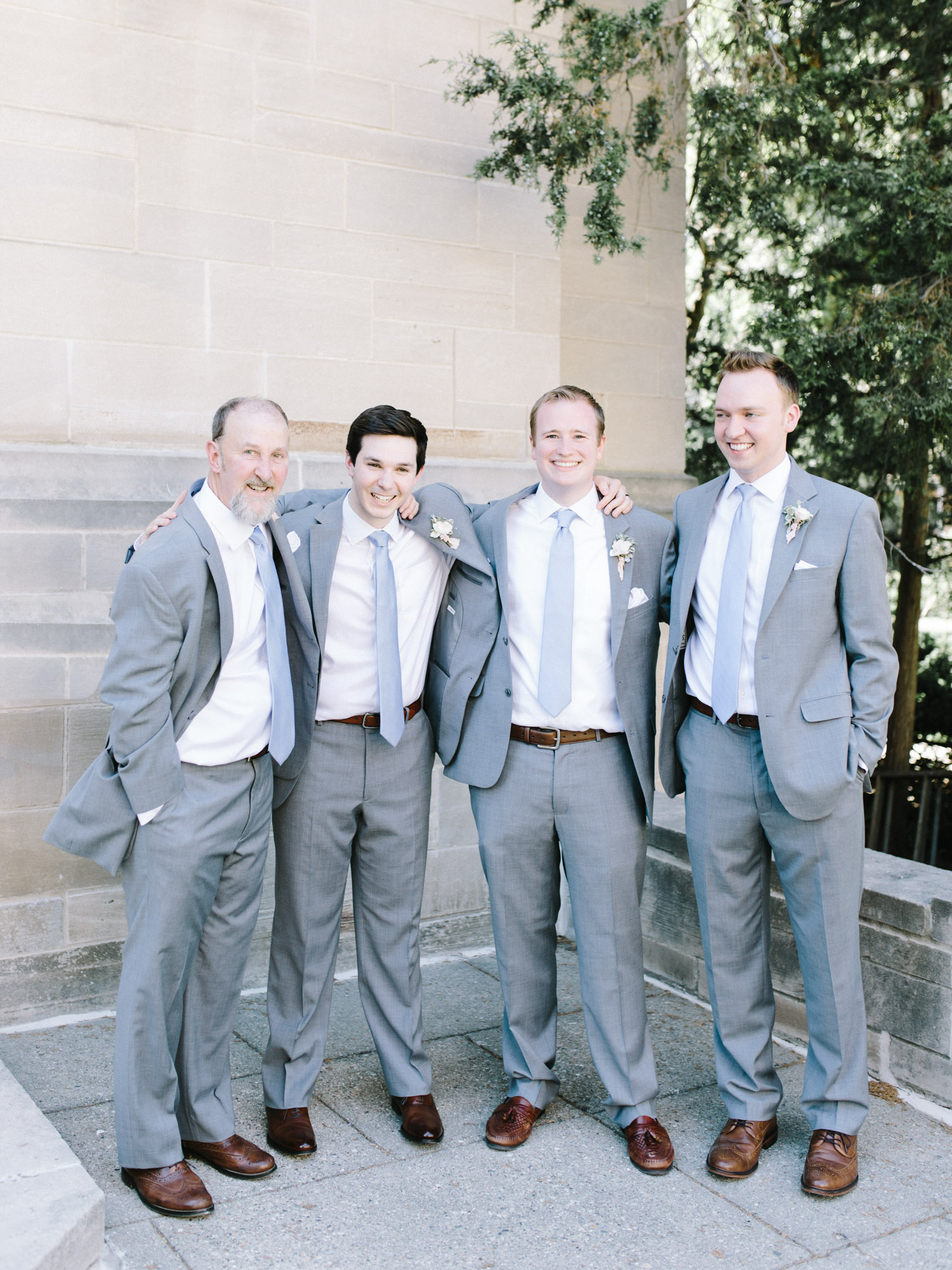Smiling groomsmen in gray tuxedos pose for a casual photo outside an Ann Arbor, Michigan church
