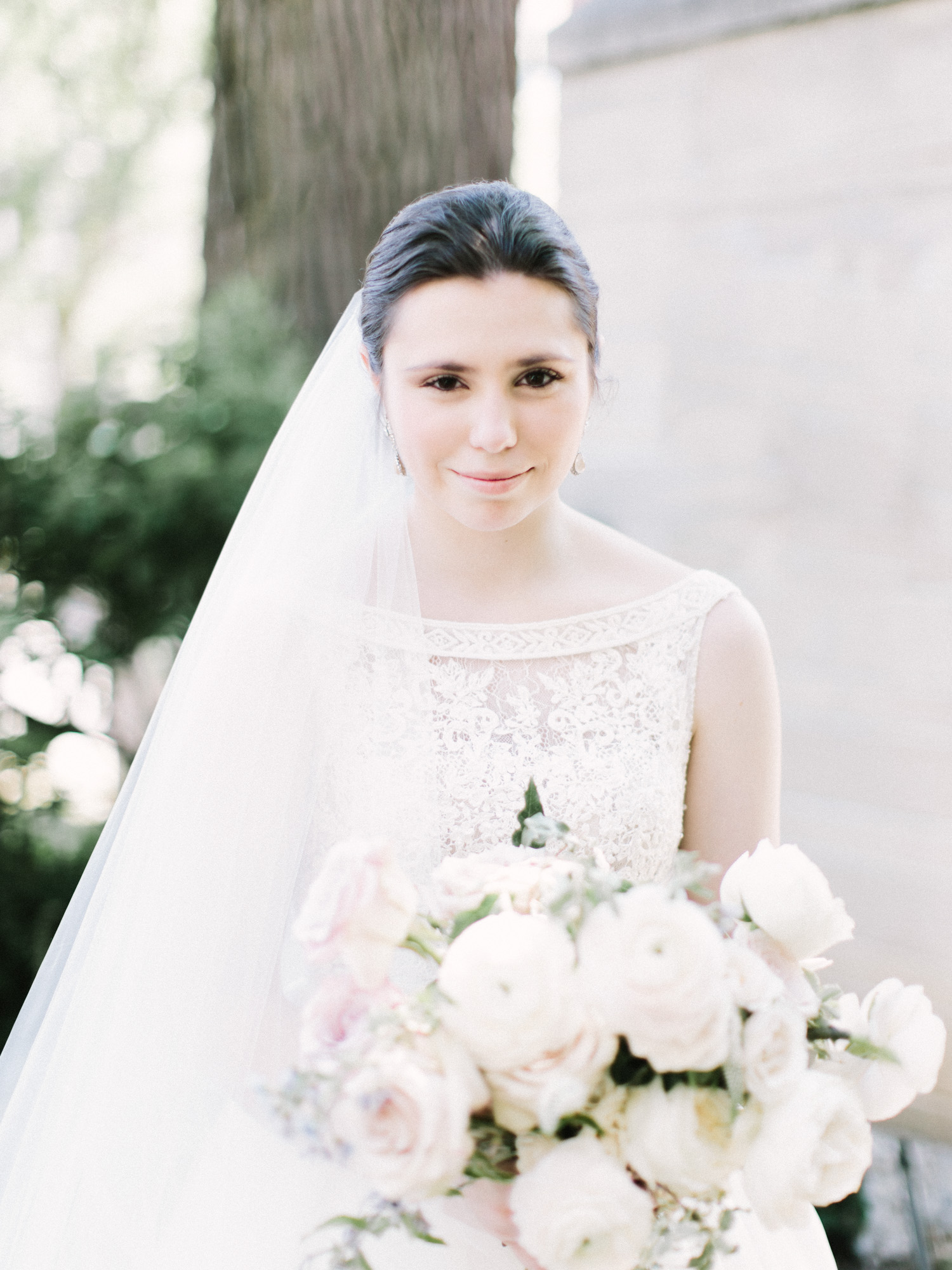 a bride in a long veil with porcelain skin and dark hair looks at the camera on her wedding day in Ann Arbor, Michigan