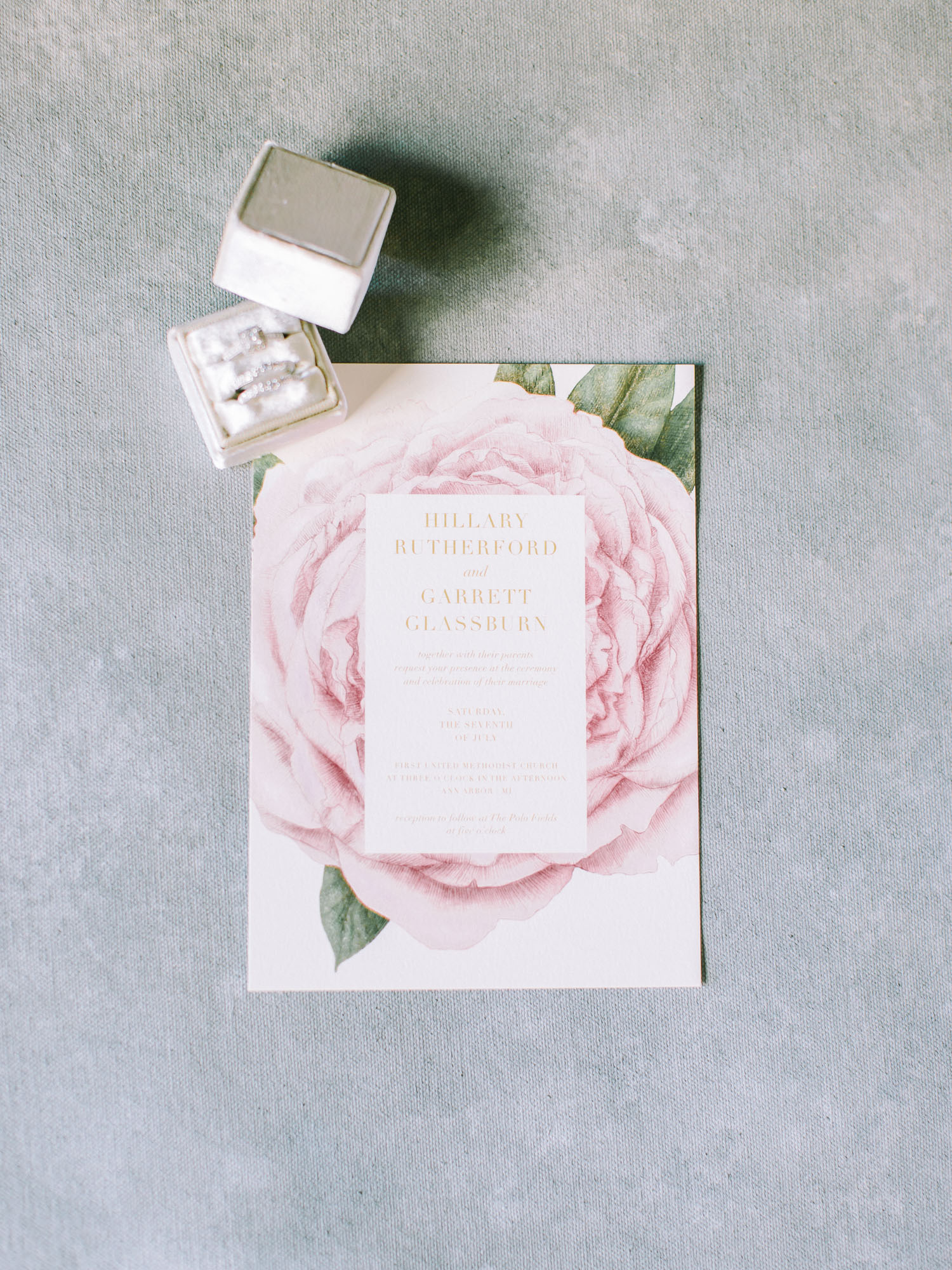 A floral wedding invitation rests on a painterly blue background along with a diamond ring in a velvet box in Ann Arbor, Michigan