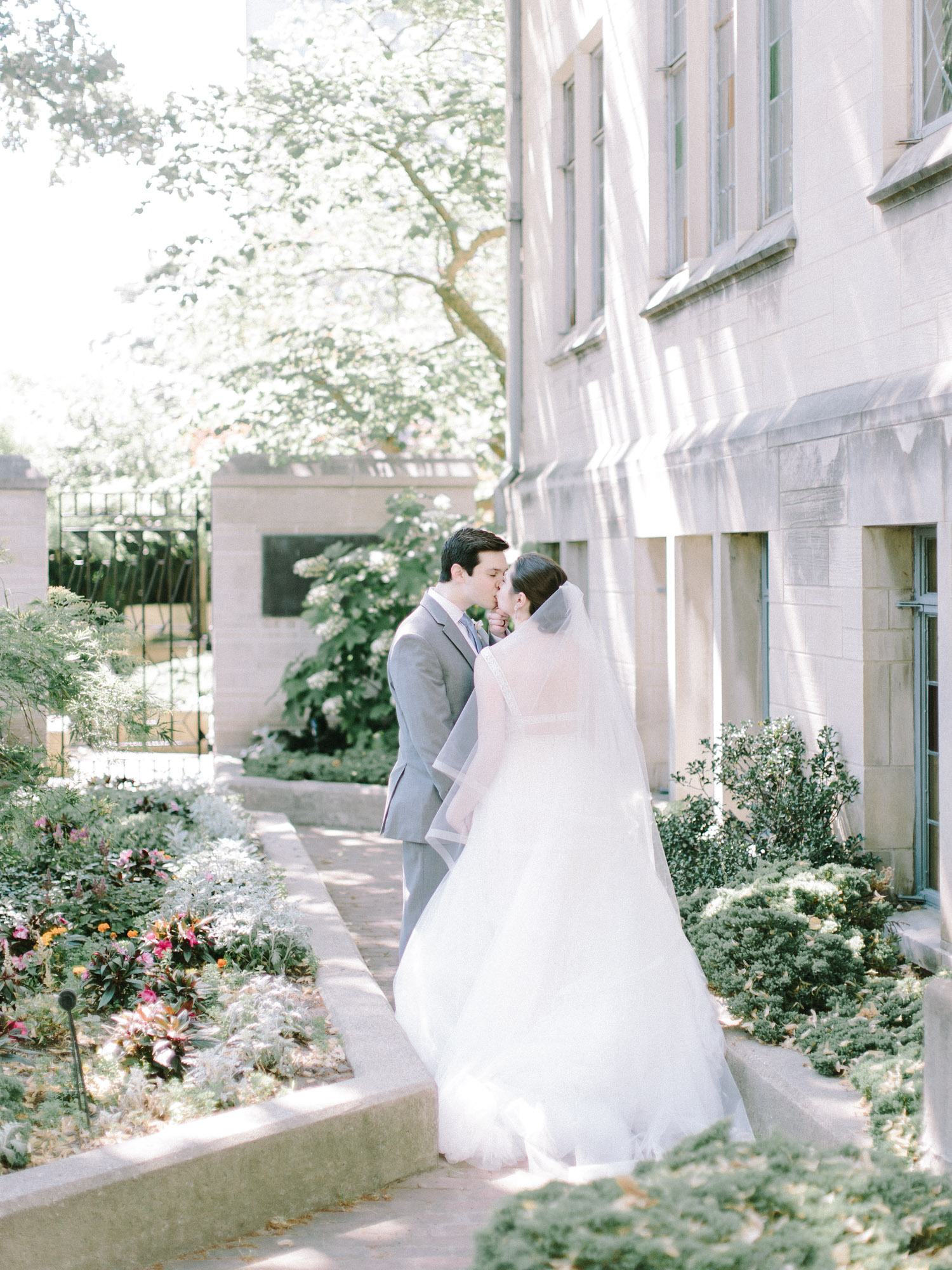 A groom gently pulls his bride in for a kiss in the gardens outside an Ann Arbor, Michigan church