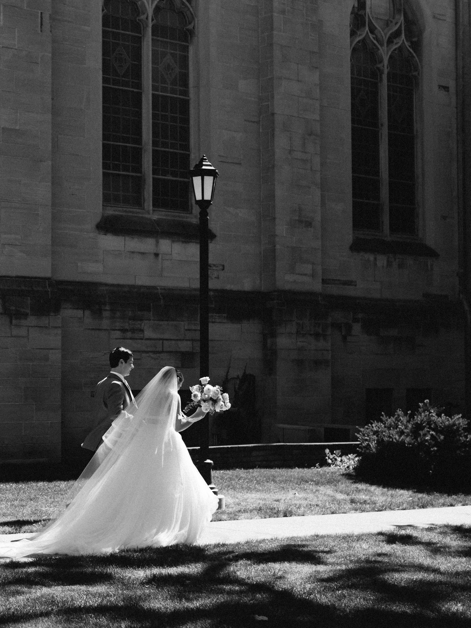 A newlywed couple walks together in sunlight outside an Ann Arbor, Michigan church