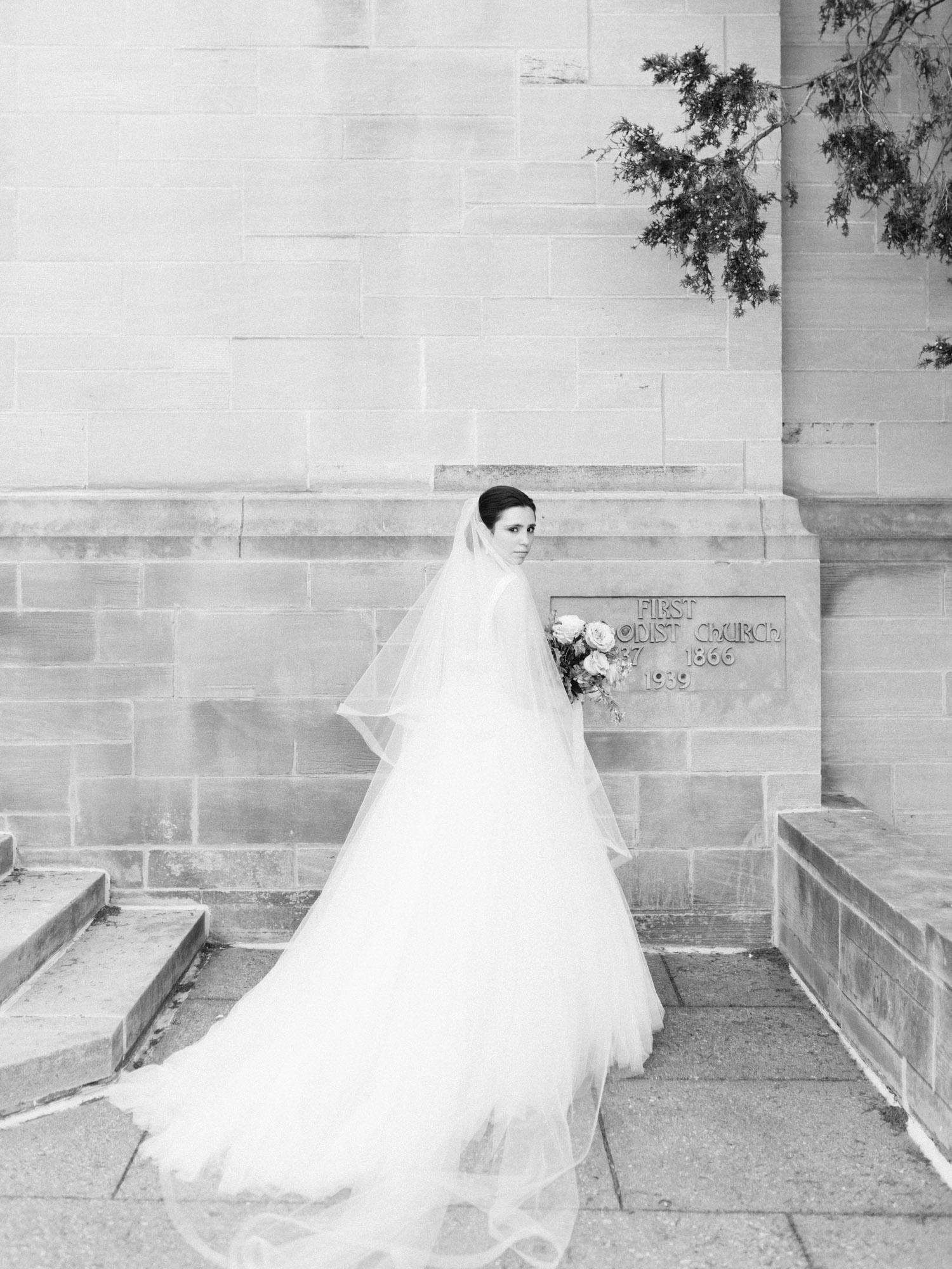 A bride with a long veil and train turns to look at the camera outside an Ann Arbor, Michigan wedding venue