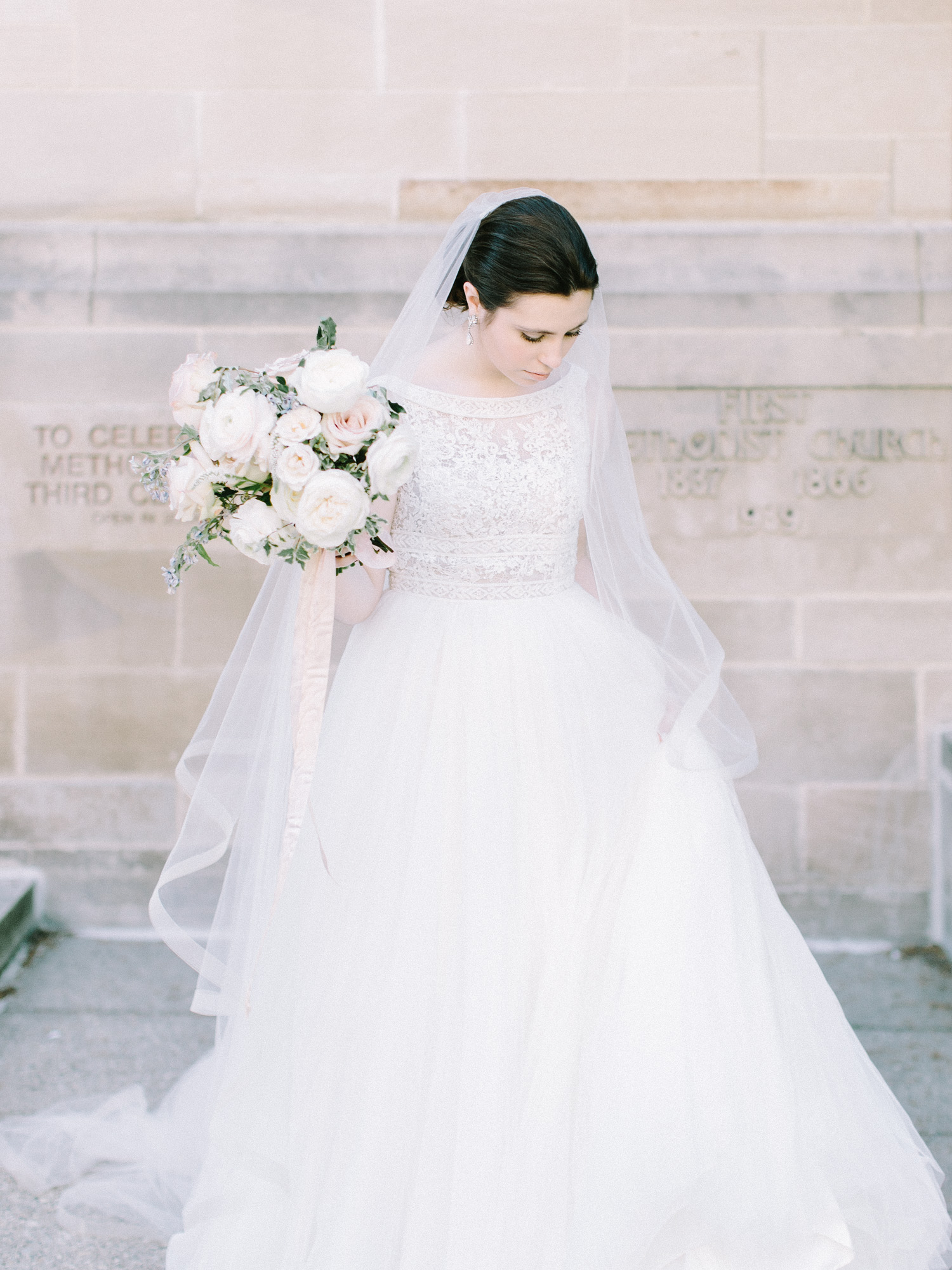 A bride in a long veil and tulle Rosa Clara gown on her wedding day in Ann Arbor, Michigan