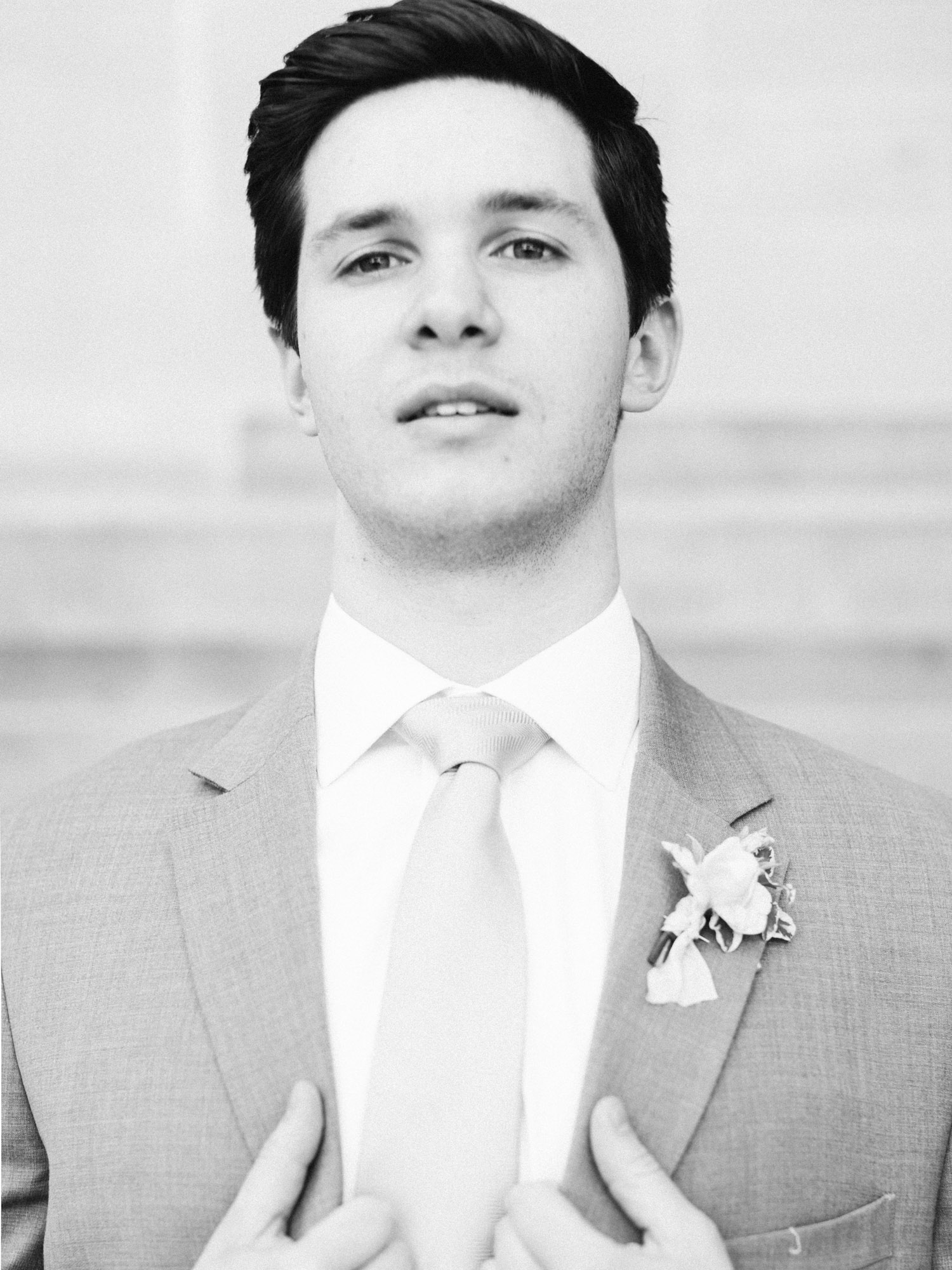 A black and white portrait of a groom as he adjusts his jacket