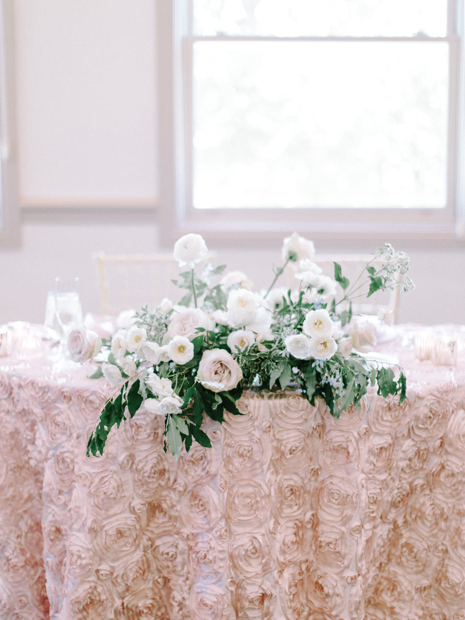 A romantic sweetheart table with simple decor and greenery at the Polo Fields in Ann Arbor, Michigan