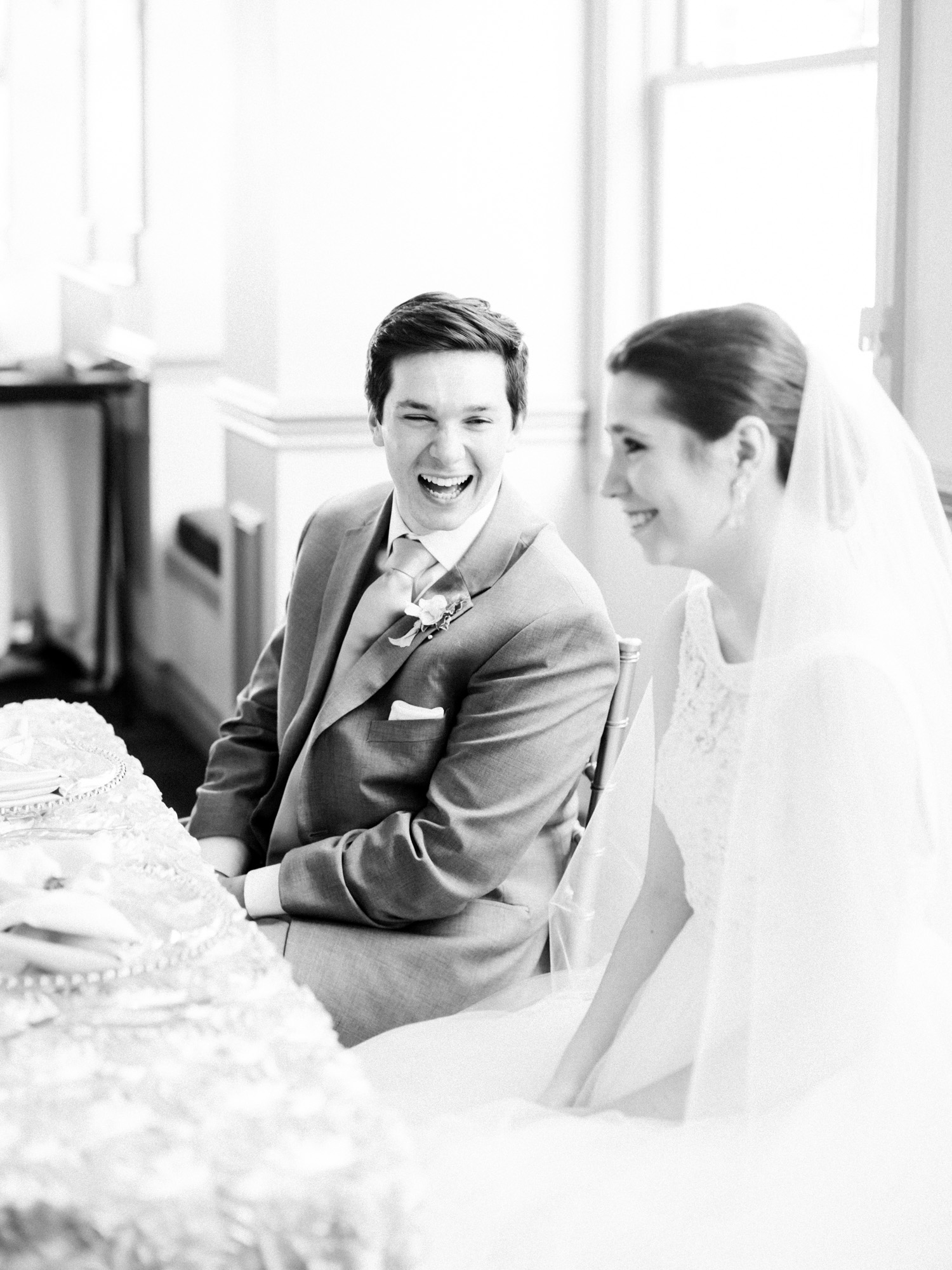 A groom laughs with his bride at their sweetheart table at The Polo Fields wedding venue in Ann Arbor