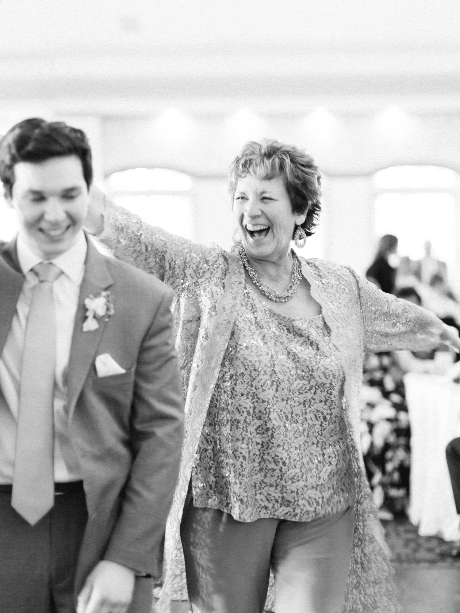 A groom and his mother laugh while dancing at his wedding reception at The Polo Fields venue in Ann Arbor, Michigan