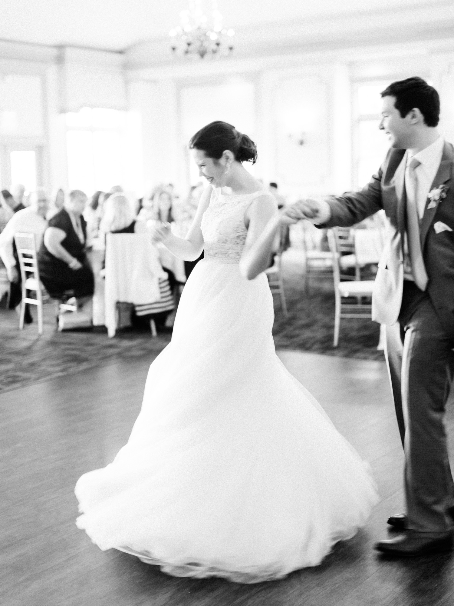 A groom twirls his bride on the dance floor at The Polo Fields in Ann Arbor