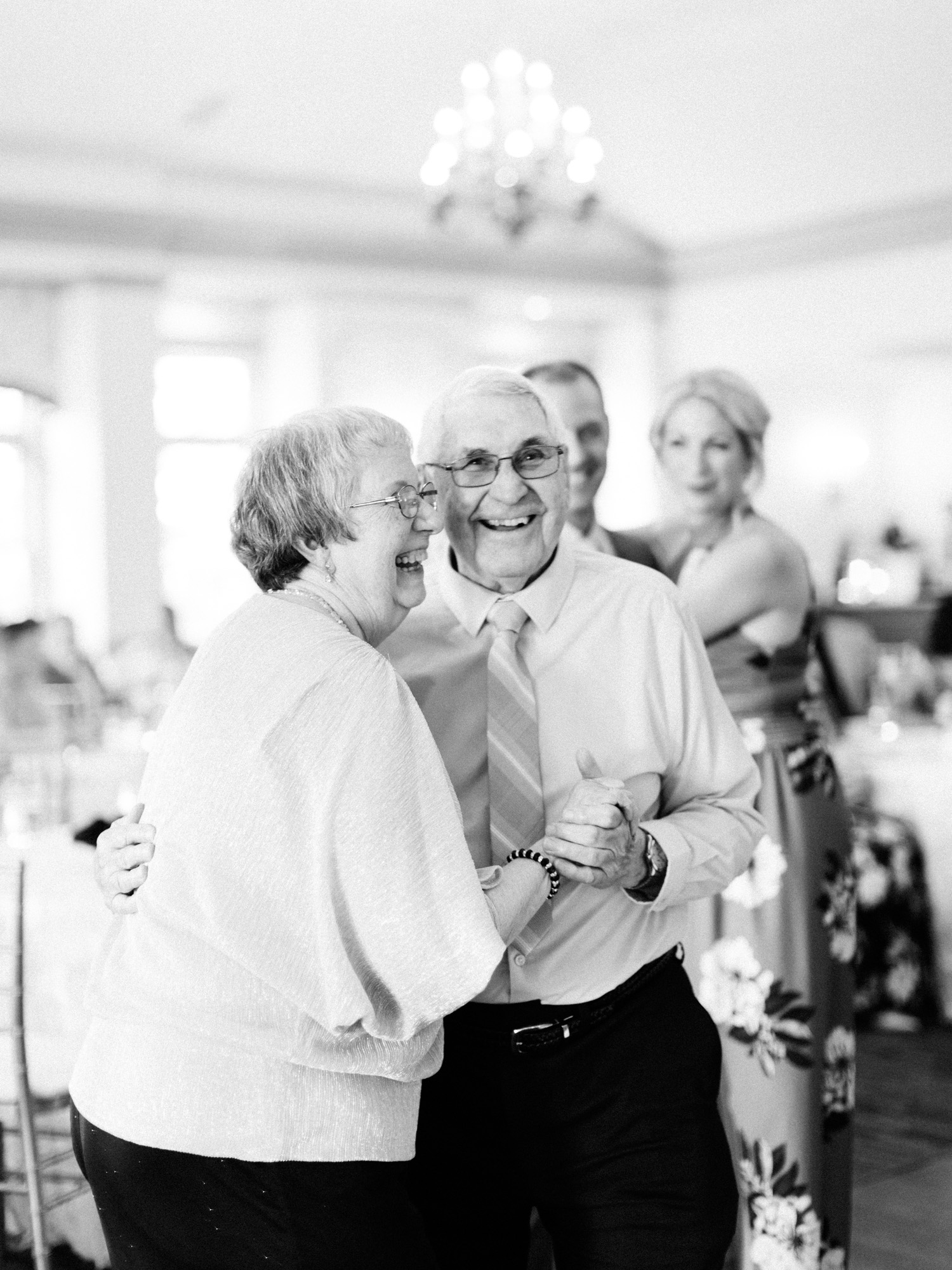 An elderly grandma and grandpa laugh while dancing together at a wedding at The Polo Fields in Michigan