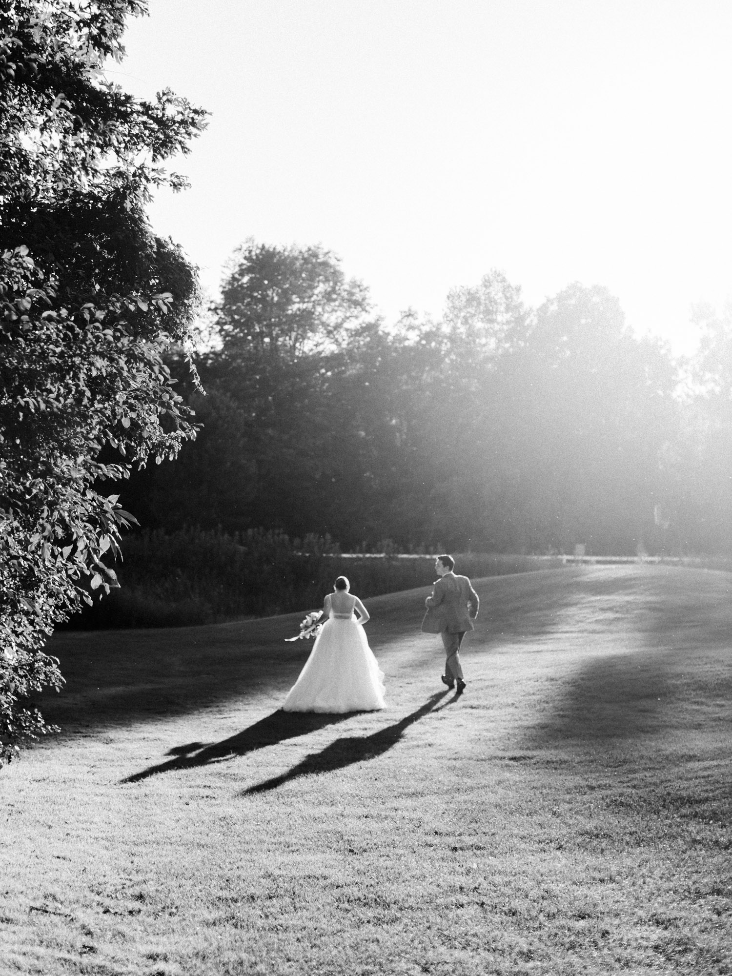 A bride and groom run off into the sunset on black and white film in Ann Arbor, Michigan