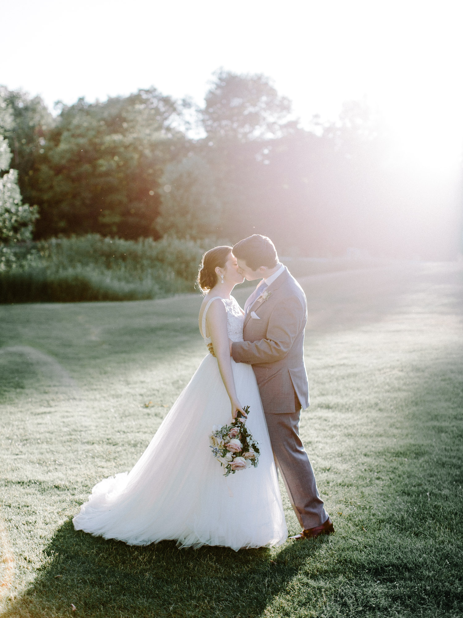 A bride and groom share a kiss in golden hour light at The Polo Fields wedding venue in Ann Arbor