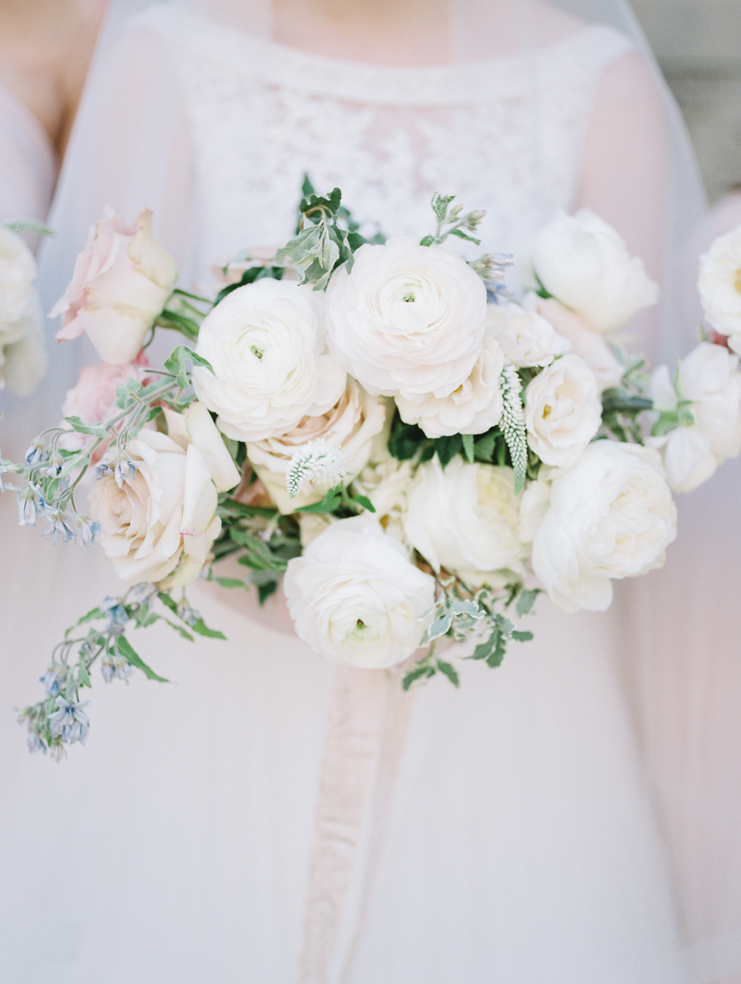 A lush bridal bouquet with white ranunculus, blush garden roses, and trailing silk ribbon by Detroit film wedding photographer Christina Harrison